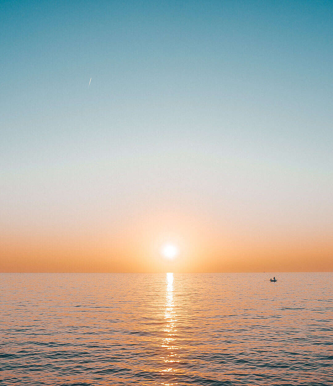 Download Sunset over the Sea with a Small Boat FREE Stock Photo