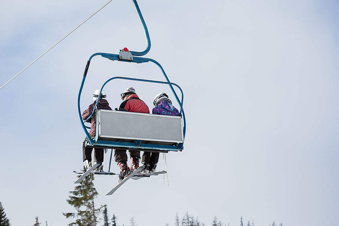 Download Three Skiers on Ski Lift FREE Stock Photo