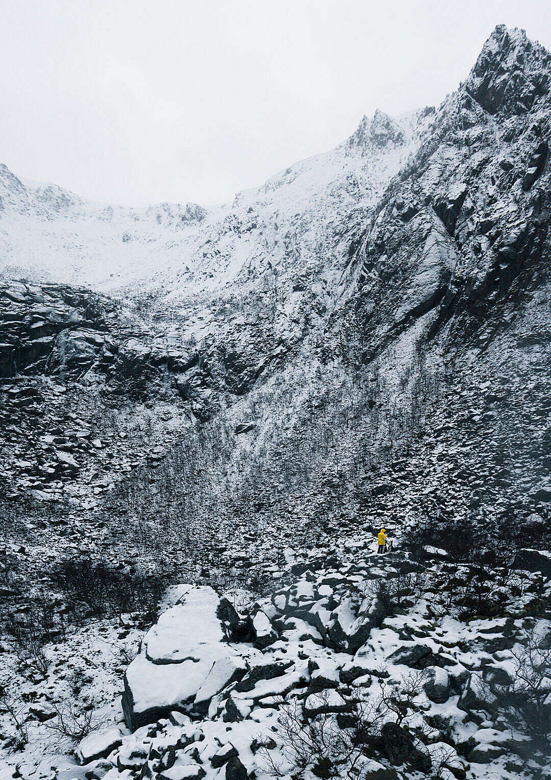 Download Tiny Person in Yellow Jacket Standing between Rocks Covered by Snow FREE Stock Photo