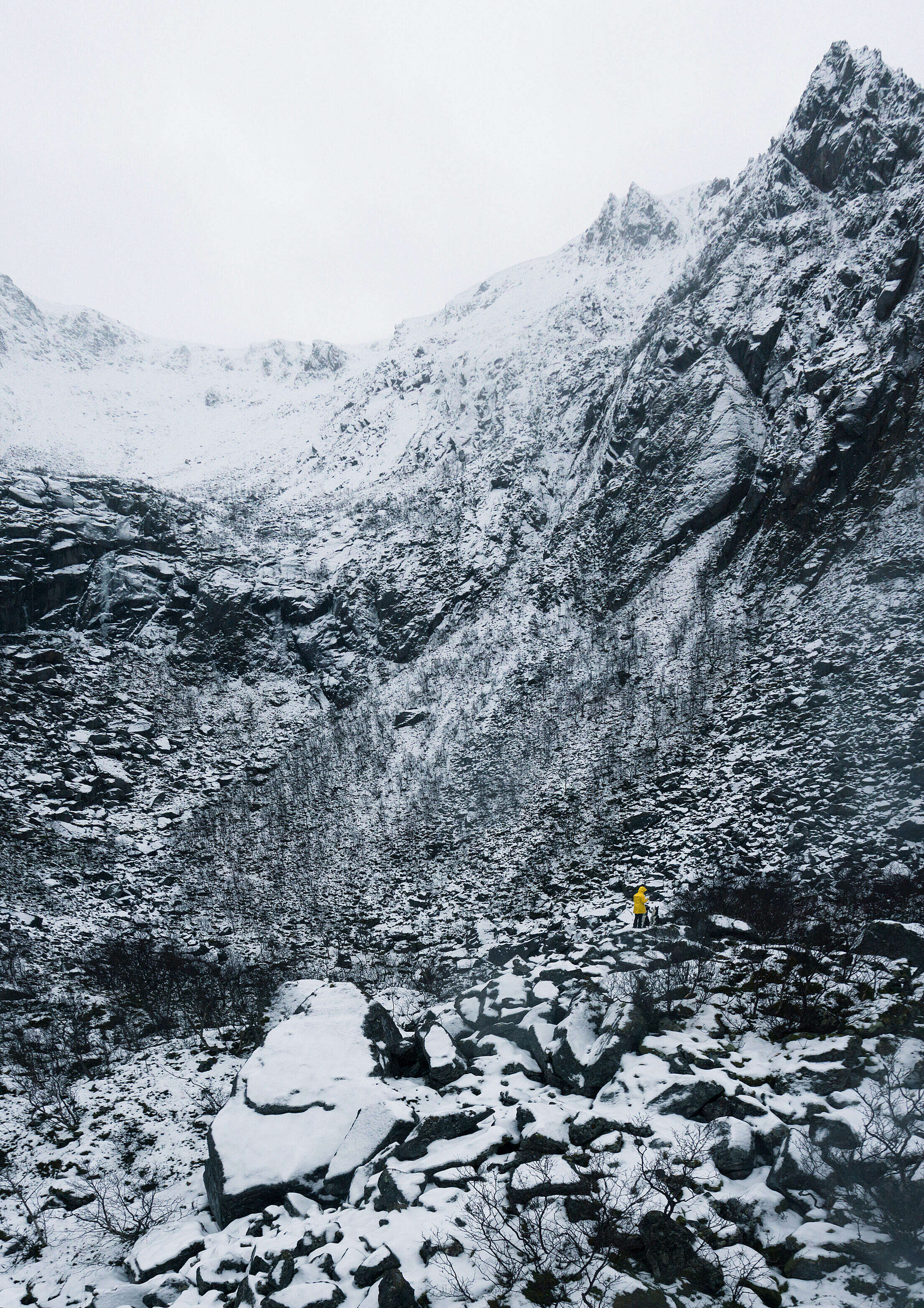 Tiny Person in Yellow Jacket Standing between Rocks Covered by Snow Free Stock Photo