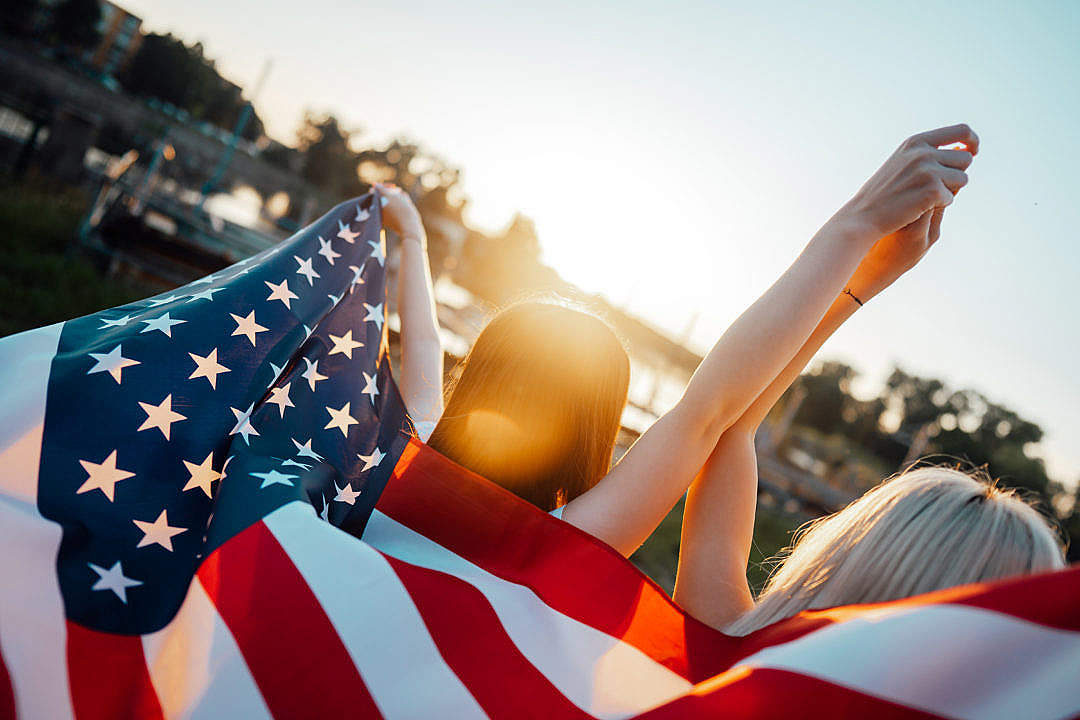 Download Two Happy Women Walking with USA Flag on Independence Day FREE Stock Photo