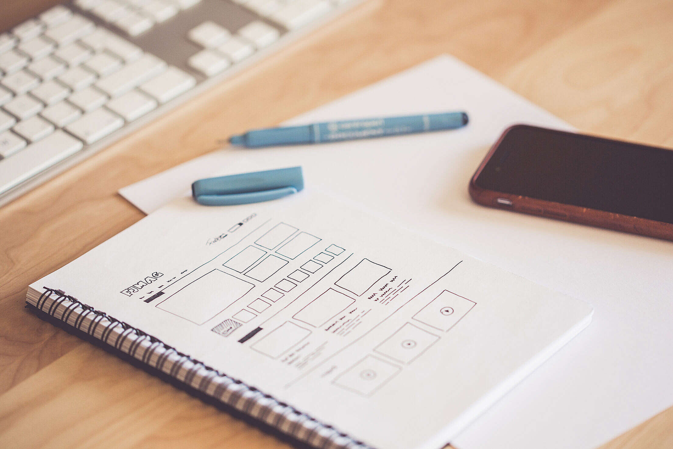 Web Designer Sketching a Wireframe Layout Ideas in a Notebook Free Stock Photo