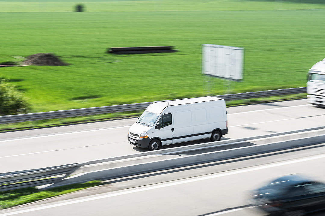 Download White Delivery Van in Motion Driving on Highway FREE Stock Photo