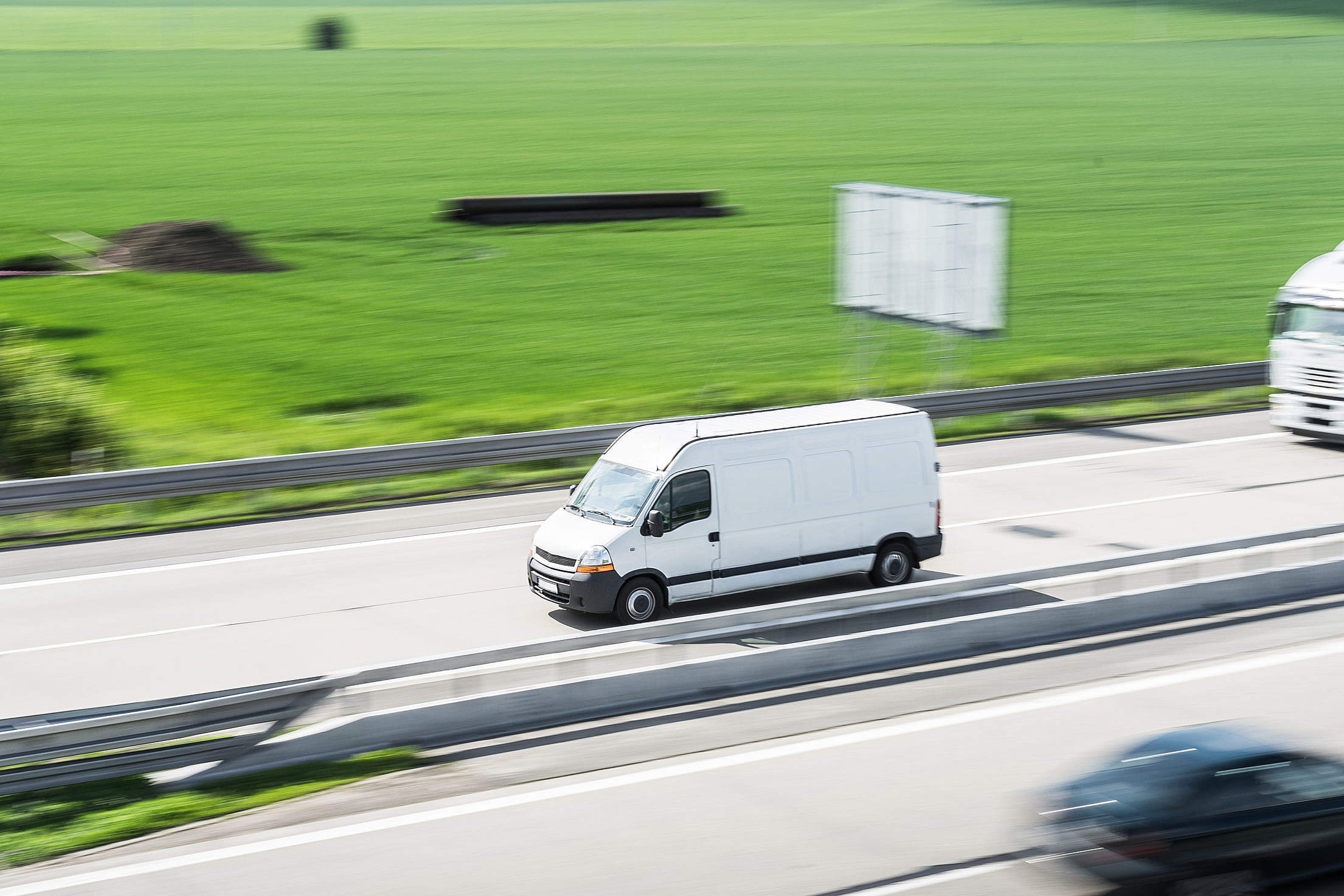 White Delivery Van in Motion Driving on Highway Free Stock Photo