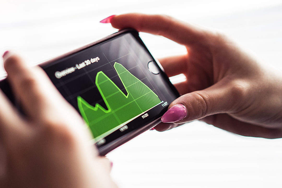 Download Woman Checking Her Website Stats On Her Smartphone FREE Stock Photo