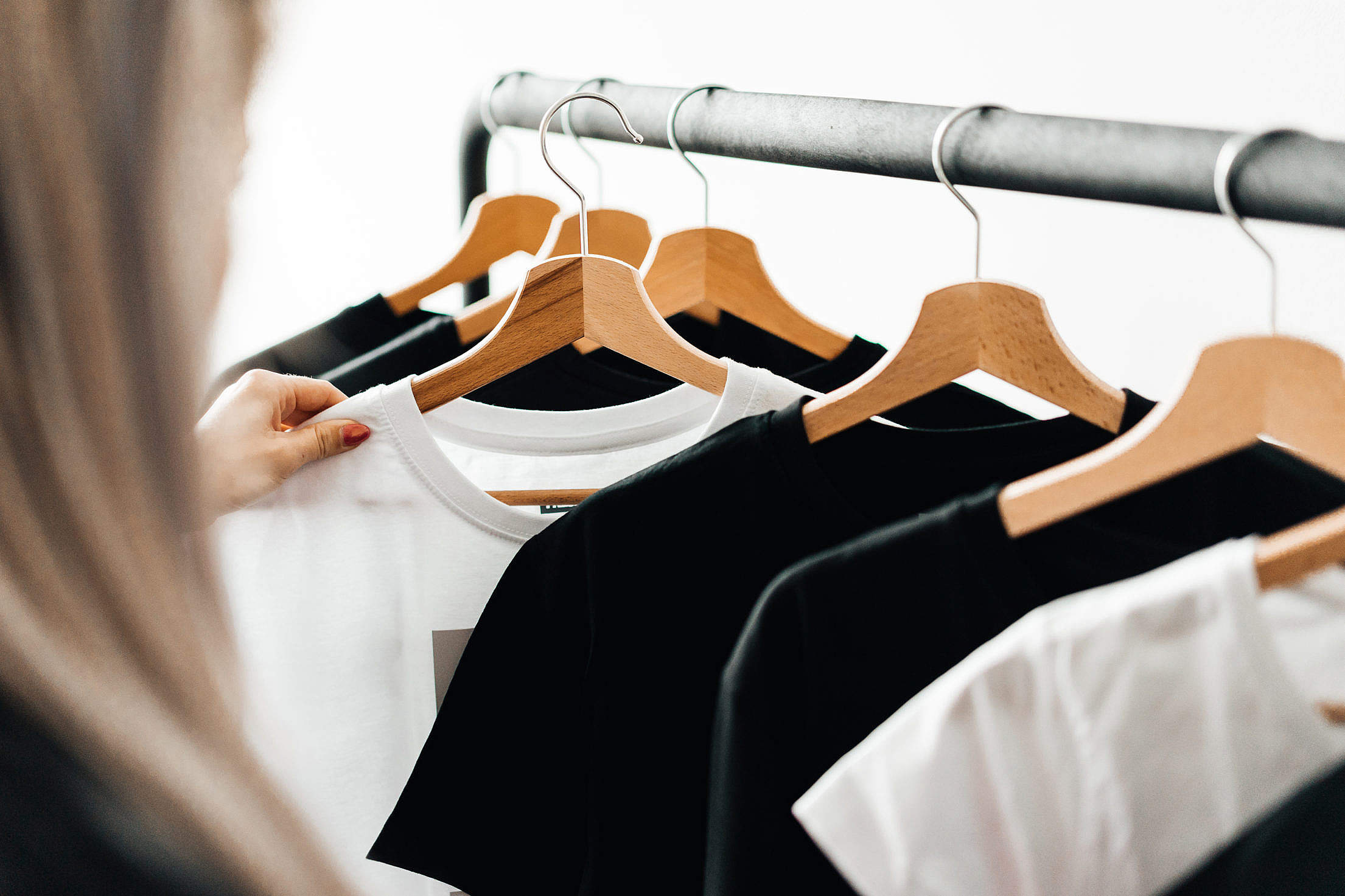 Download Woman Choosing T-Shirts During Clothing Shopping at Apparel Store Free Stock Photo