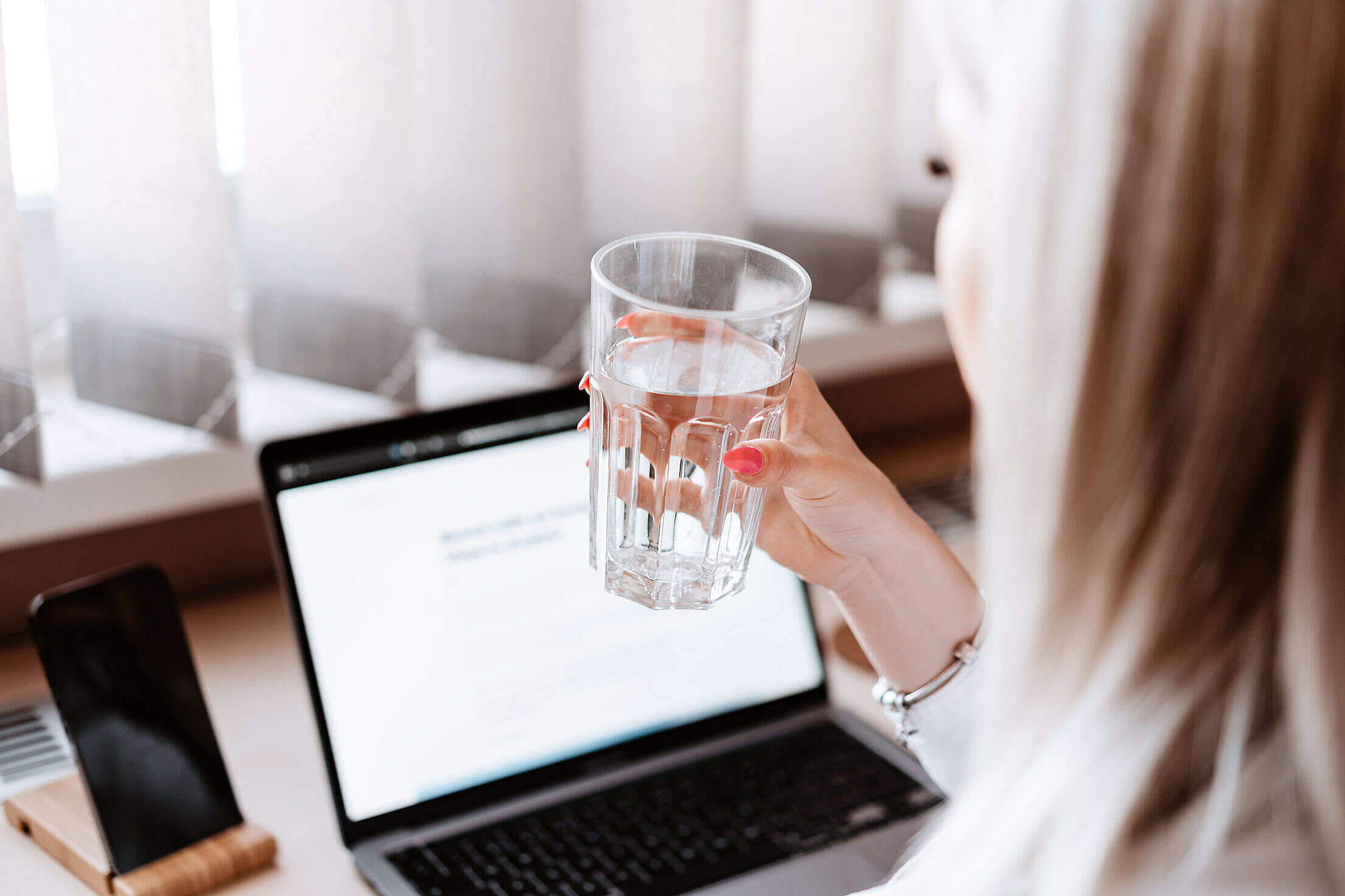Woman Drinking Still Water at Work Free Stock Photo