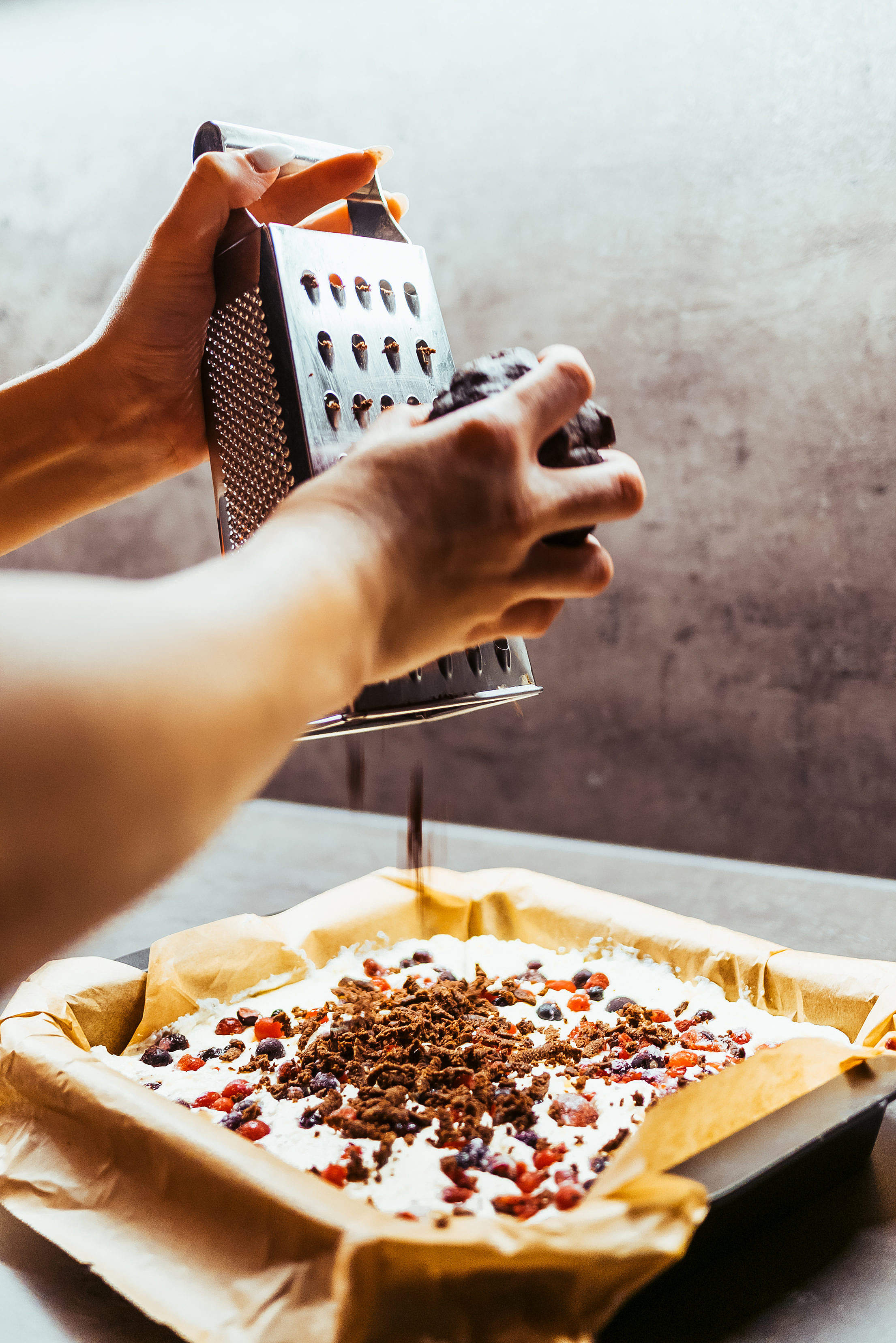 Woman Grating Chocolate on a Cake Free Stock Photo