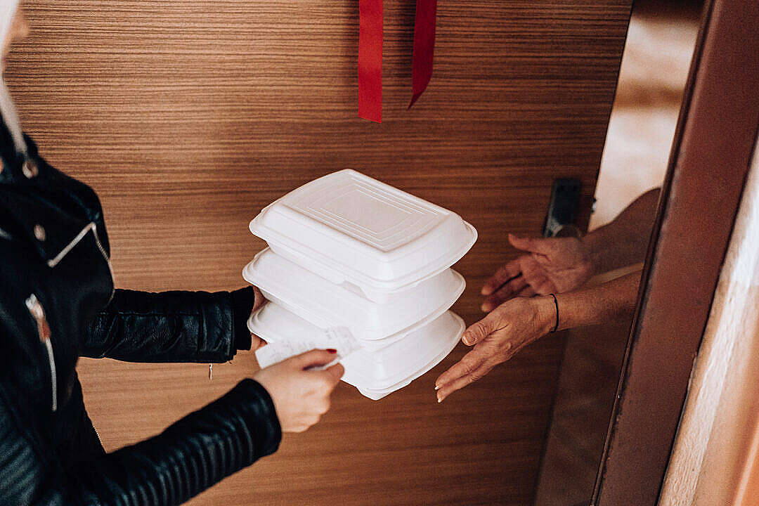 Download Woman Handing over Ordered Boxes with Food FREE Stock Photo