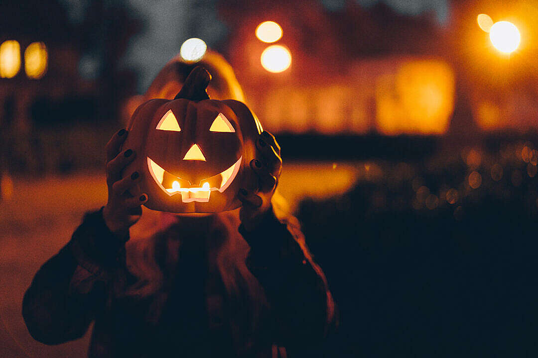 Download Woman Holding a Halloween Pumpkin in front of her Face at Night FREE Stock Photo