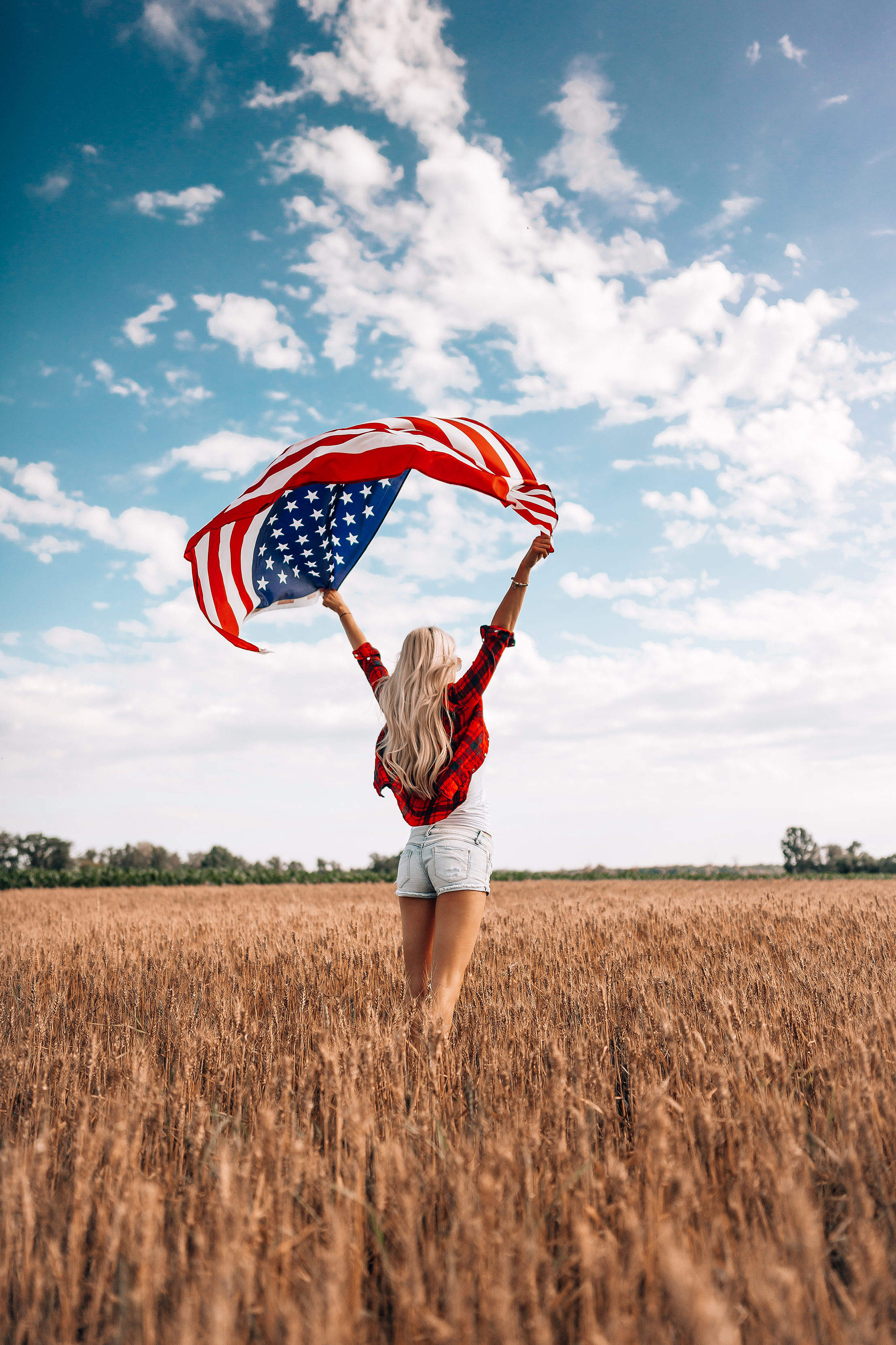 Woman Holding an American Flag in a Field Free Stock Photo