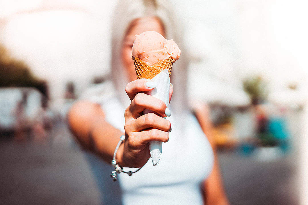 Download Woman Holding an Ice Cream in Front of Her Face FREE Stock Photo