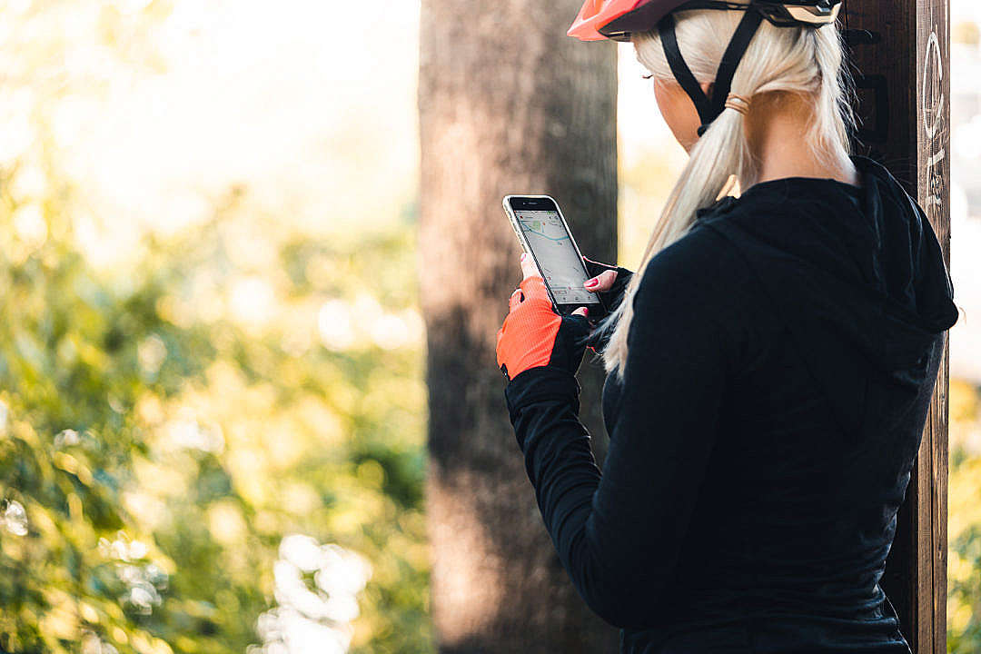 Download Woman in Cycling Clothes Looking at The Map on The Phone FREE Stock Photo