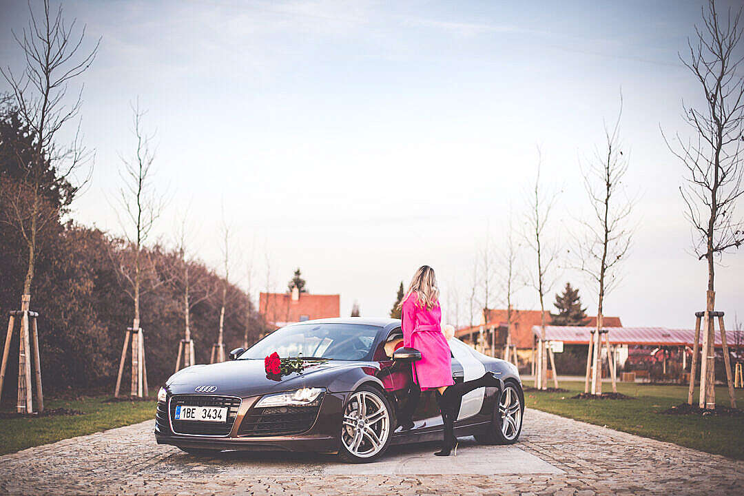 Download Woman in Pink Coat Standing Next To a Supercar FREE Stock Photo