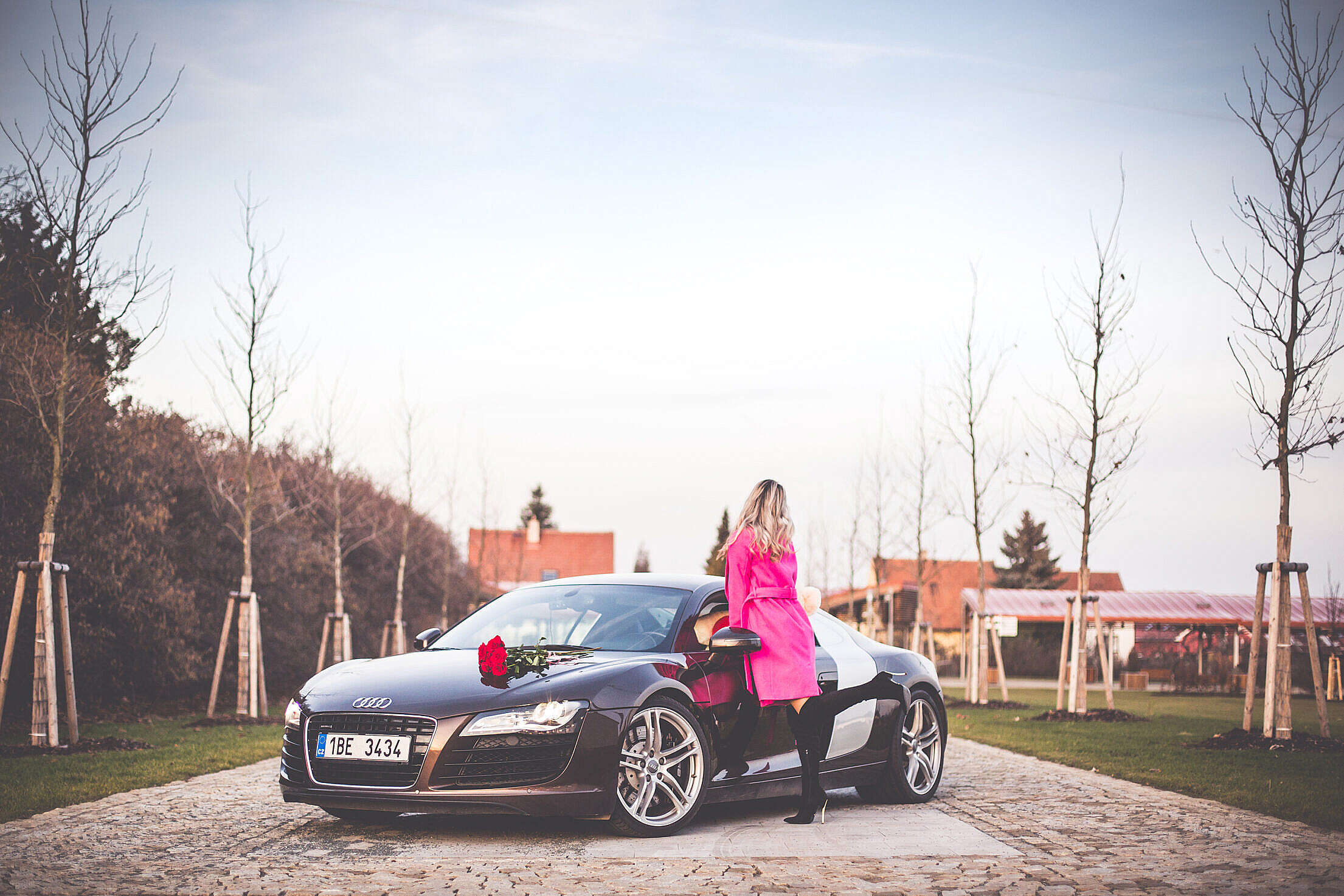 Woman in Pink Coat Standing Next To a Supercar Free Stock Photo
