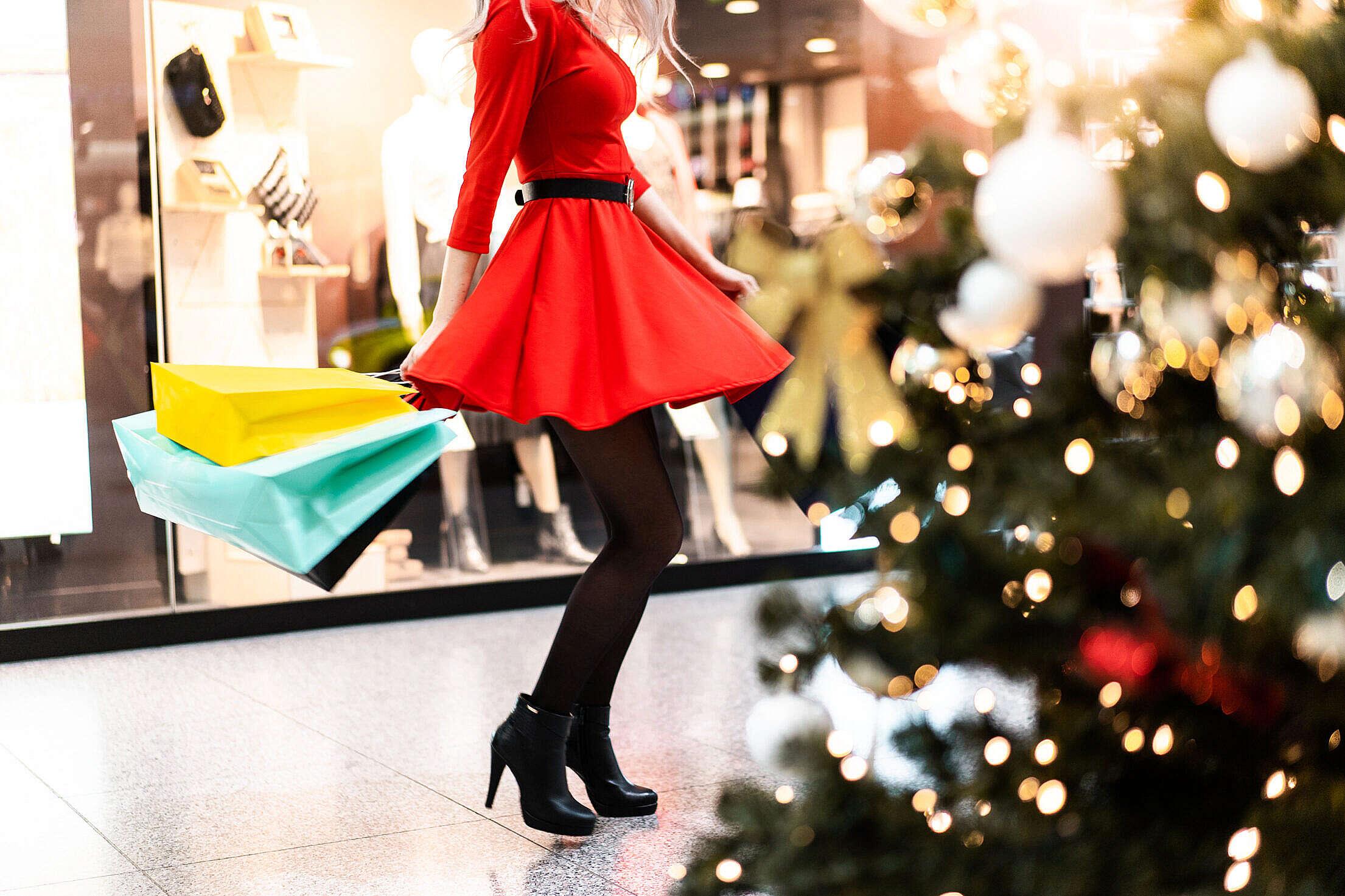 Woman in Red Dress Enjoying Christmas Shopping Free Stock Photo