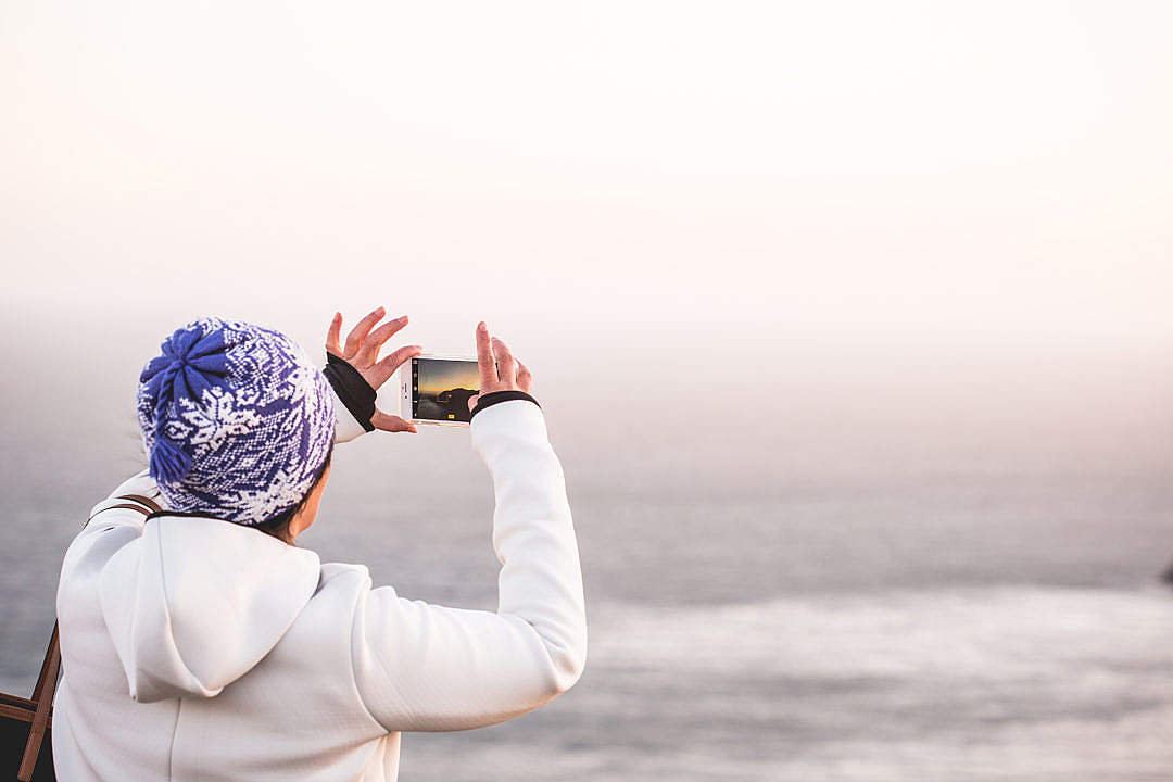 Download Woman in Winter Hat Taking a Picture of Endless Ocean FREE Stock Photo