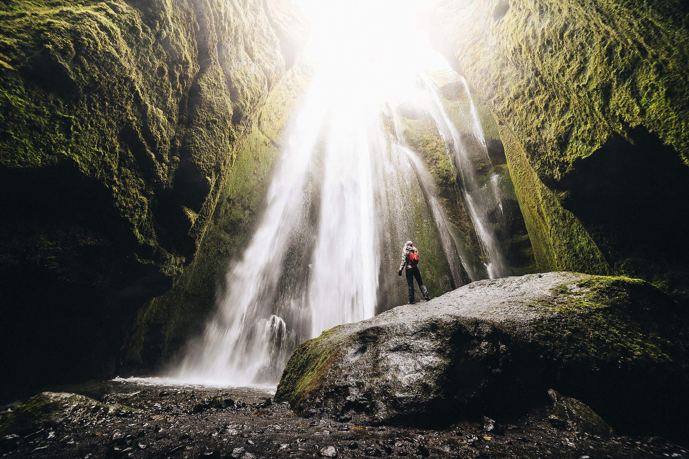 Woman Looking Up at Gljúfrabúi Waterfall Free Stock Photo