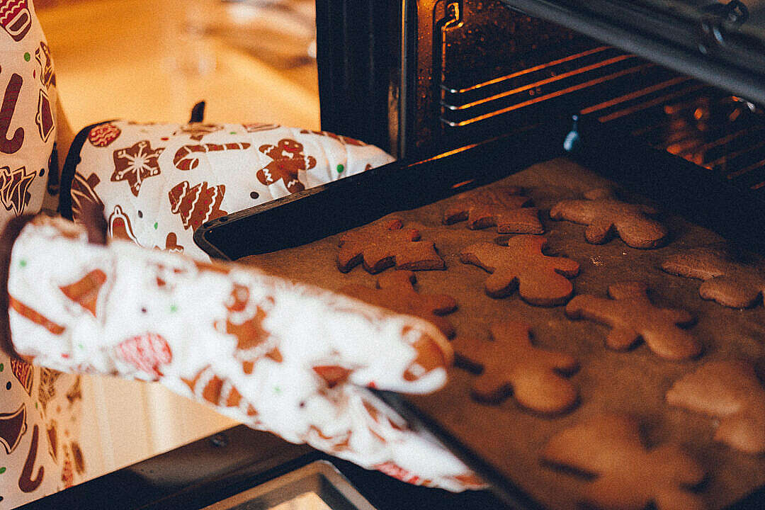 Download Woman Putting Christmas Cookies in The Oven FREE Stock Photo