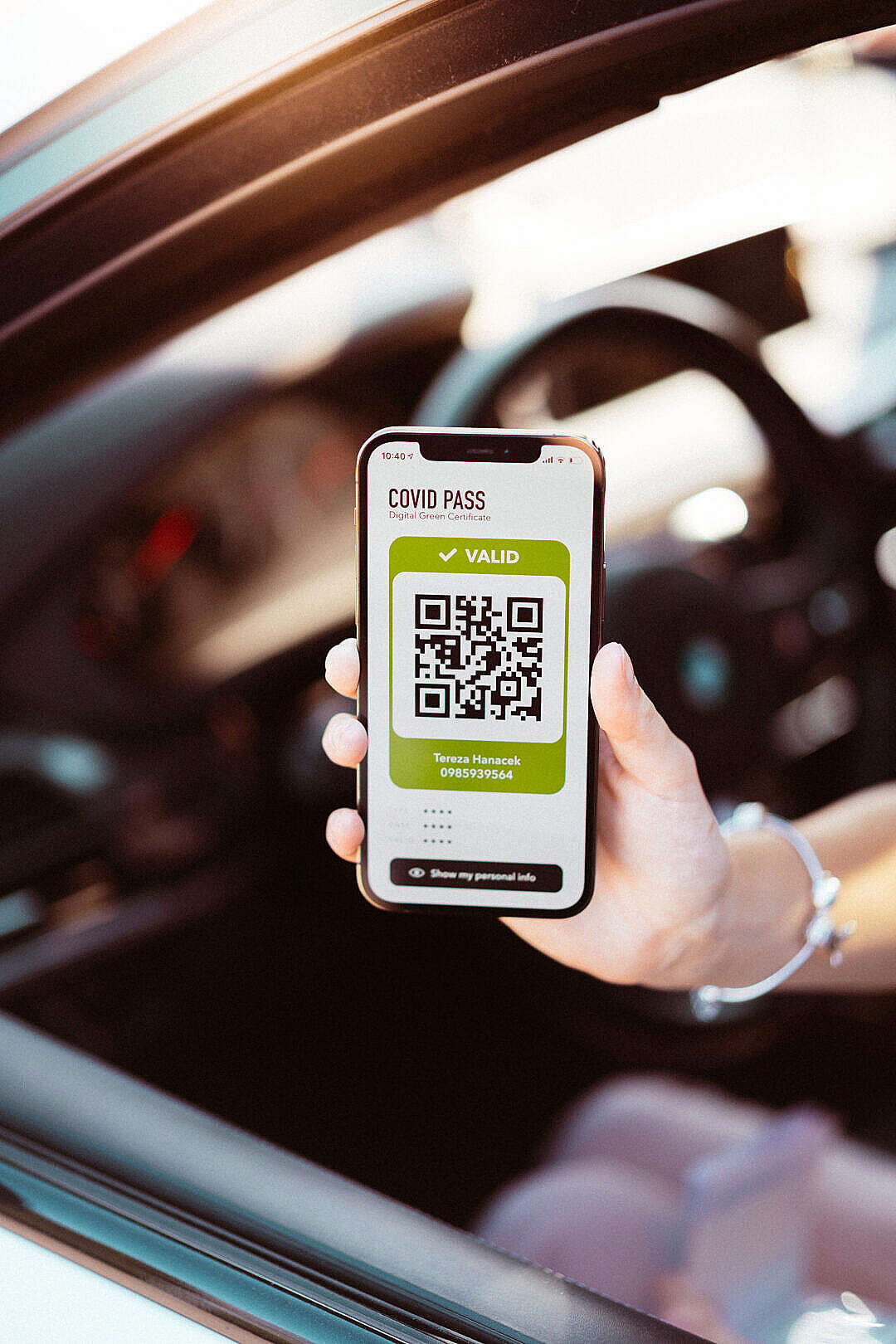 Download Woman Showing Covid Pass Certificate from Car FREE Stock Photo
