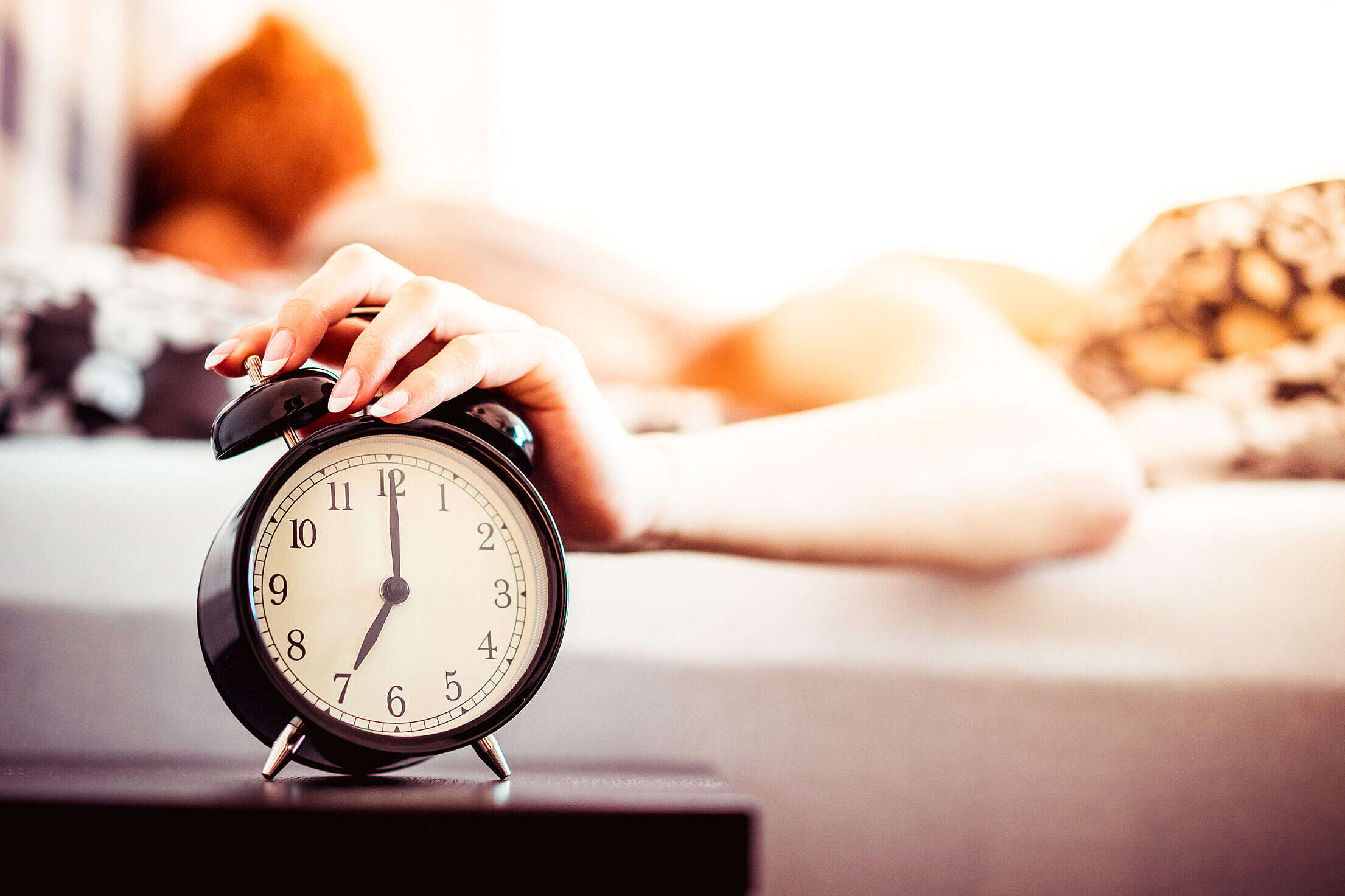 Woman Shutting Off Ringing Alarm Clock From Bed Free Stock Photo