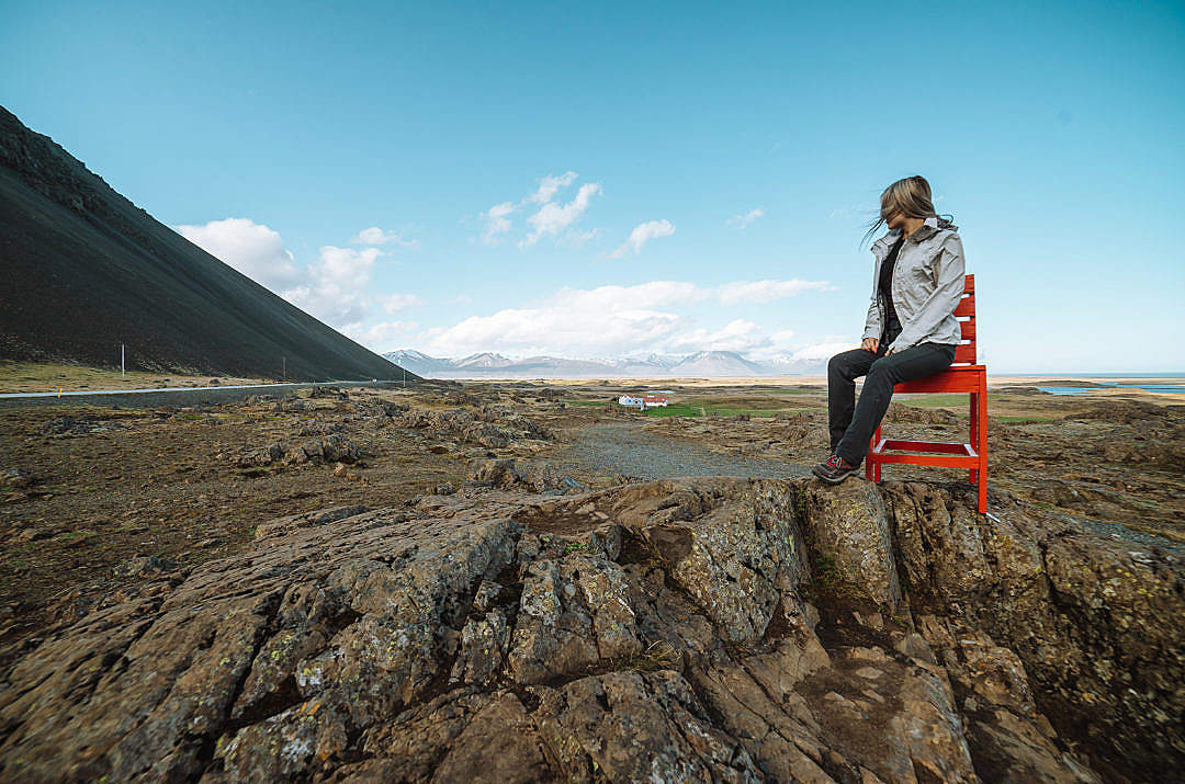 Download Woman Sitting on a Big Red Chair in Iceland FREE Stock Photo