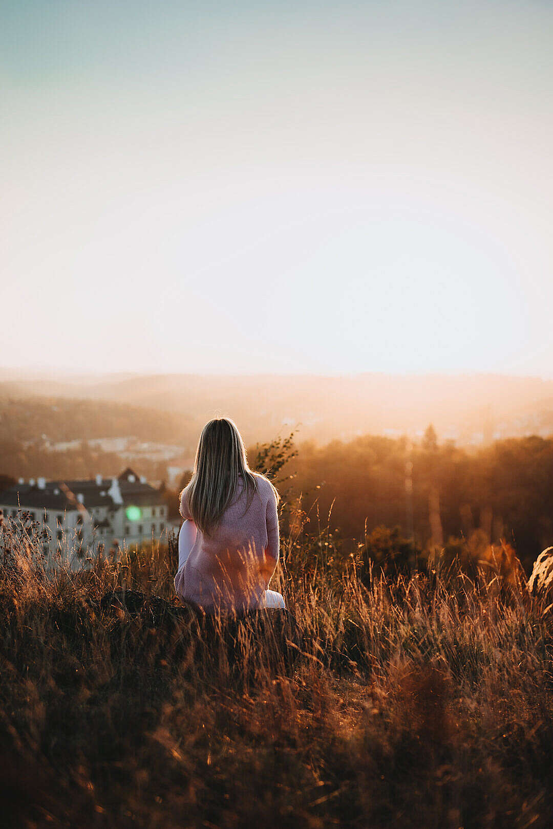 Download Woman Sitting on a Hill and Looking at The Castle FREE Stock Photo