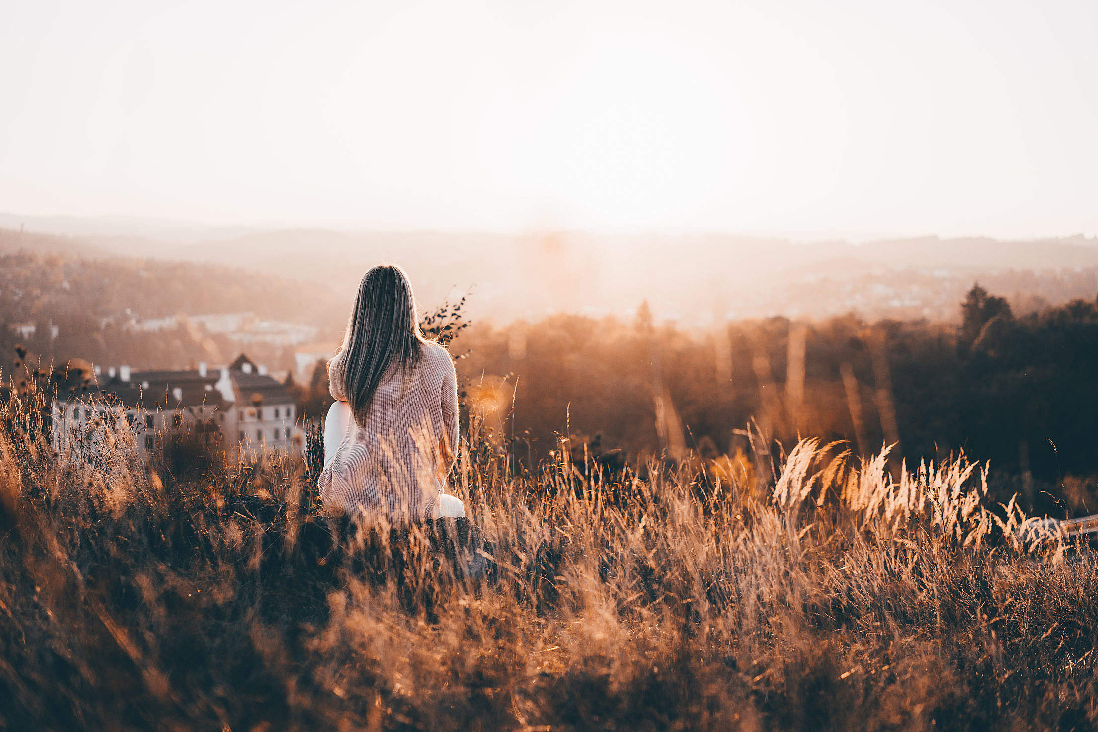 Woman Sitting on a Hill and Watching Nature Free Stock Photo