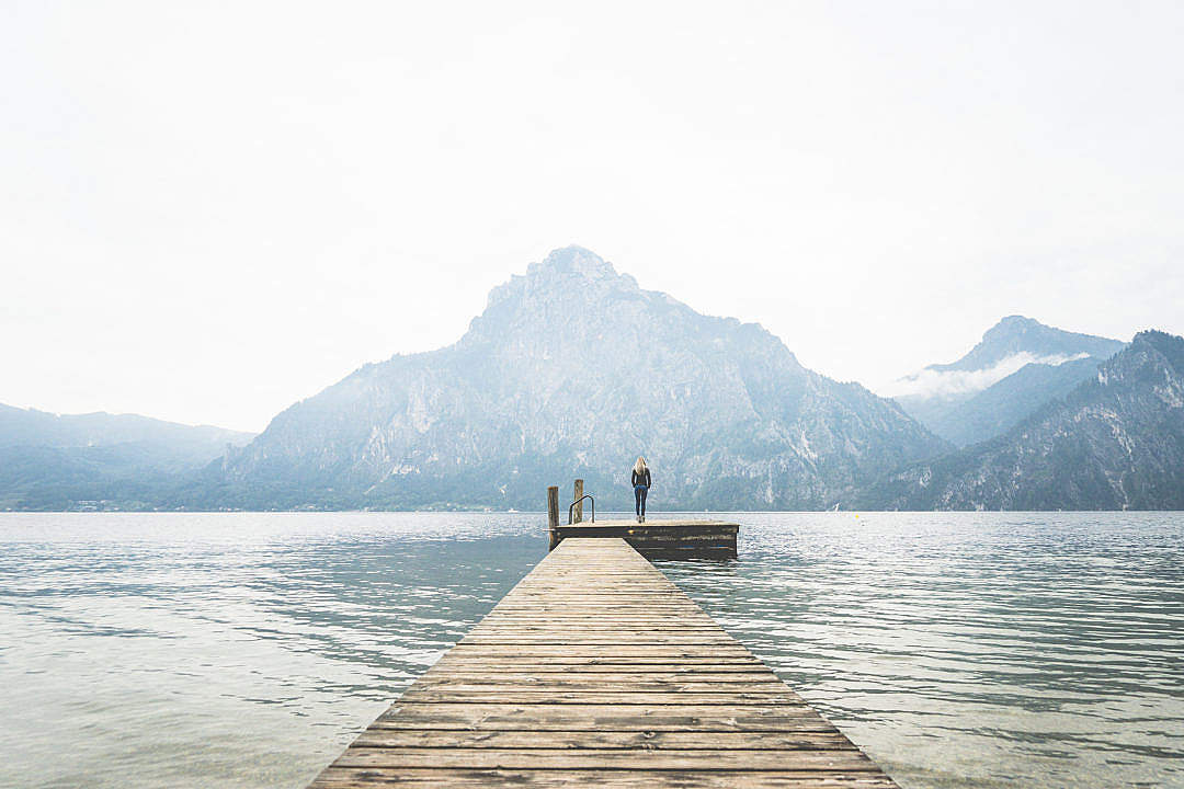 Download Woman Standing Alone on a Large Wooden Pier on a Lake FREE Stock Photo
