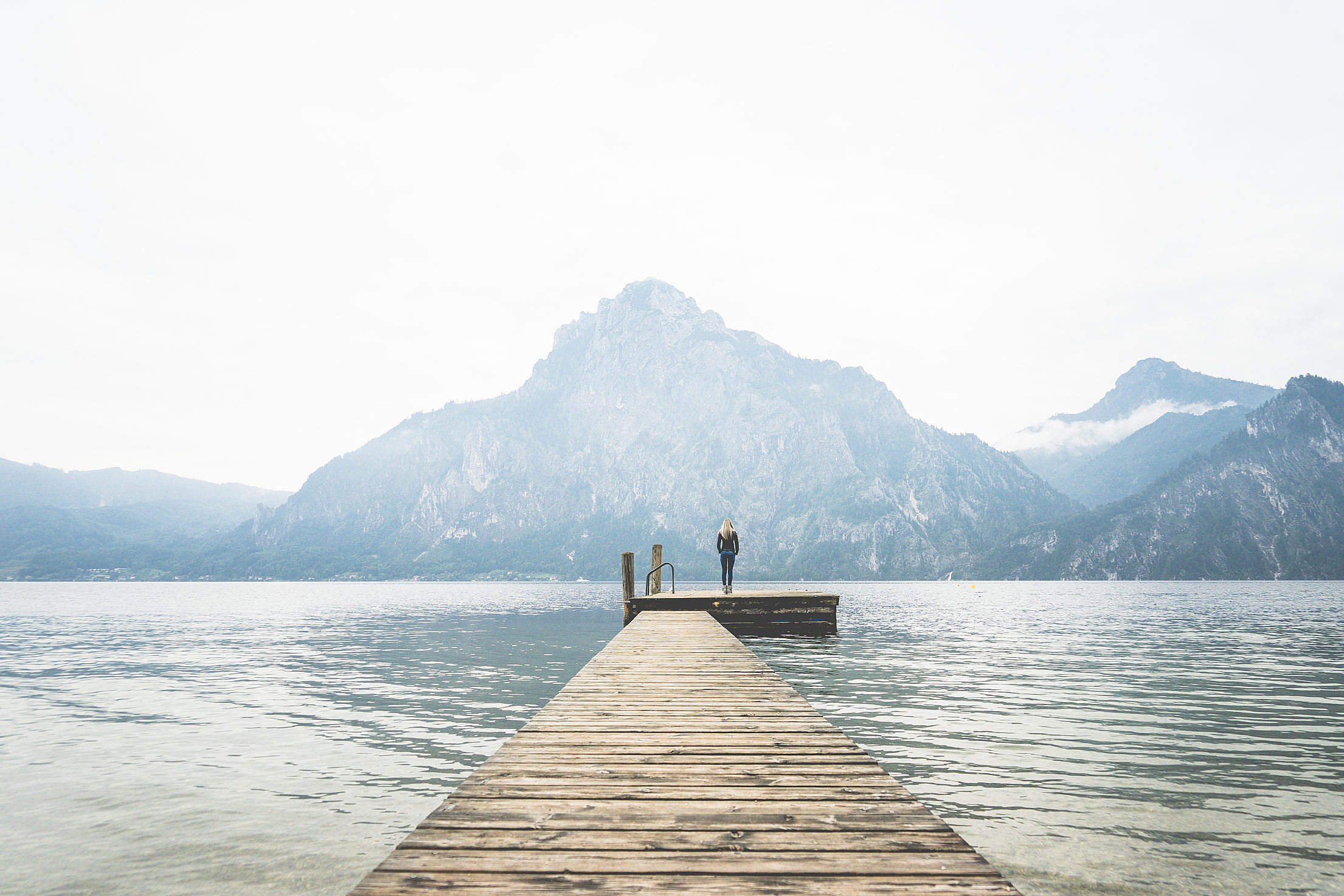 Woman Standing Alone on a Large Wooden Pier on a Lake Free Stock Photo