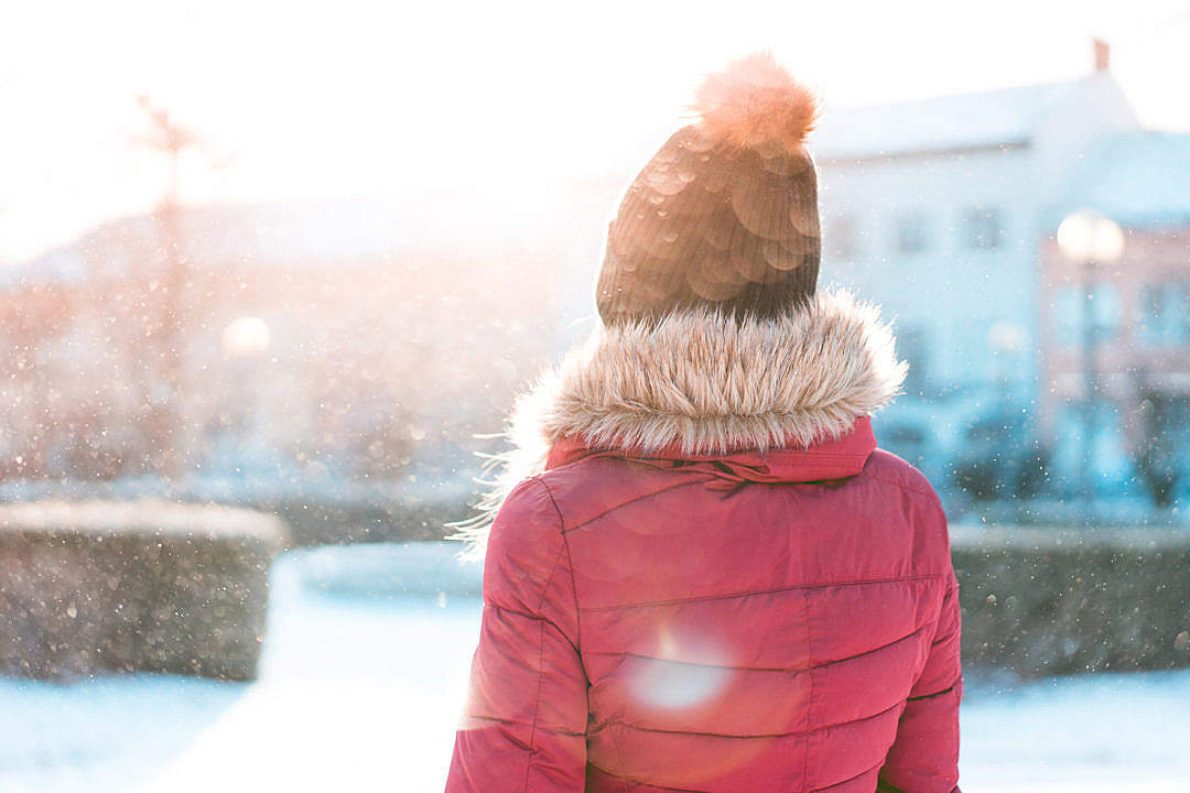 Download Woman Standing in Snowfall while Sun is Shining FREE Stock Photo