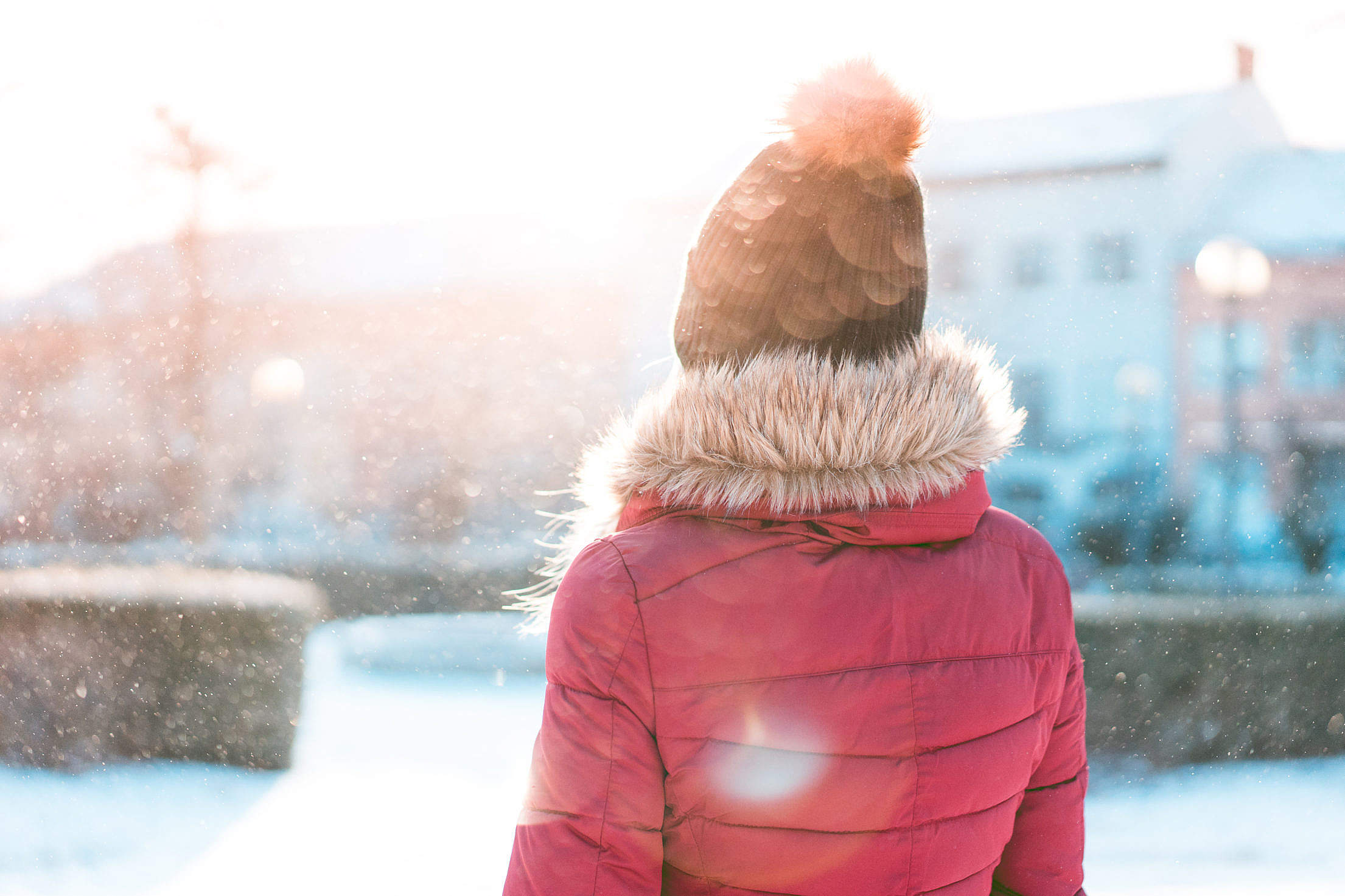 Woman Standing in Snowfall while Sun is Shining Free Stock Photo