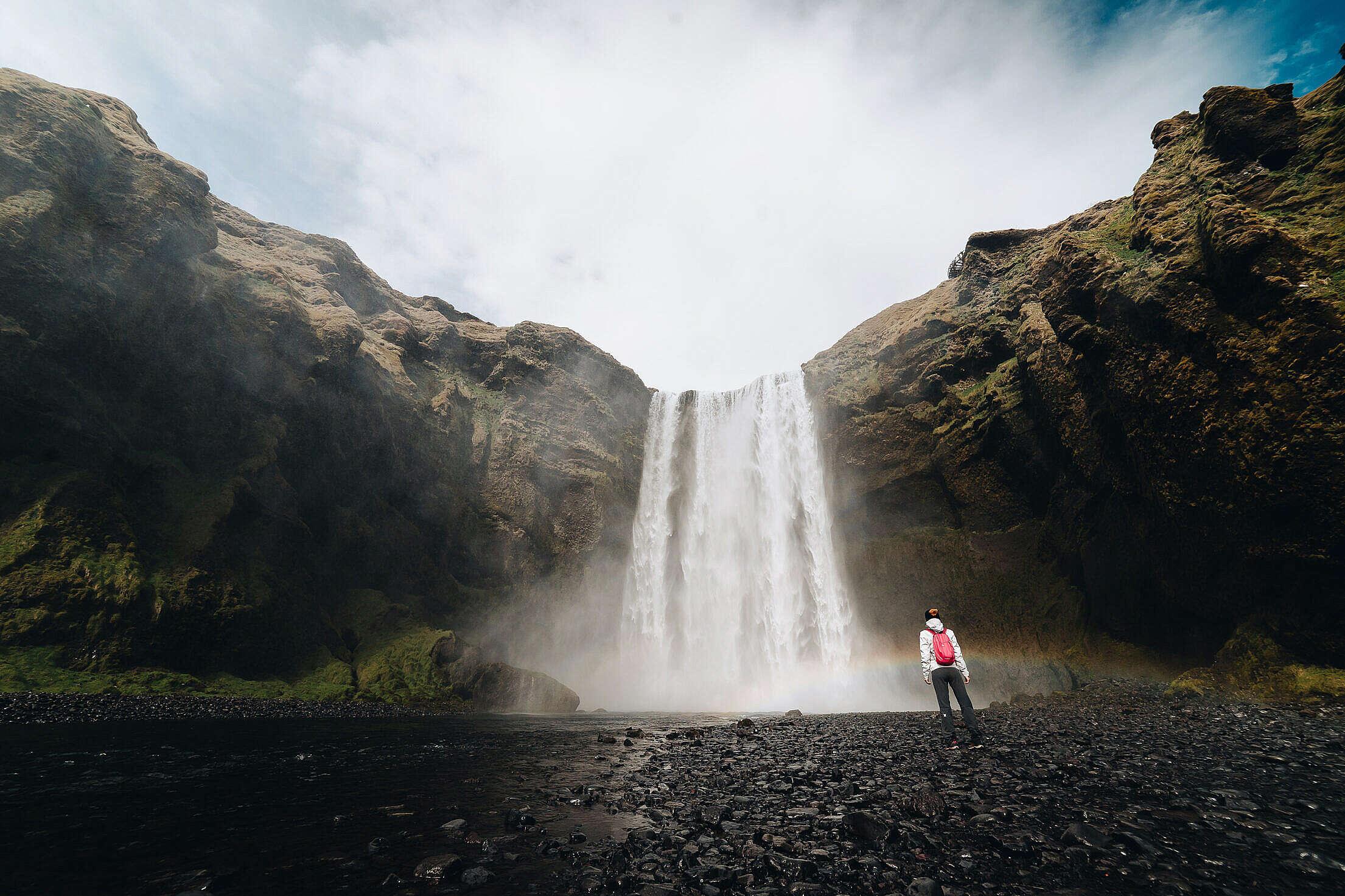 Woman Standing Near Skógafoss Waterfall Free Stock Photo