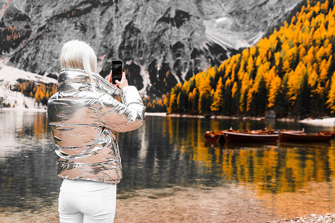 Download Woman Taking a Photo of Braies Lake in Italy FREE Stock Photo
