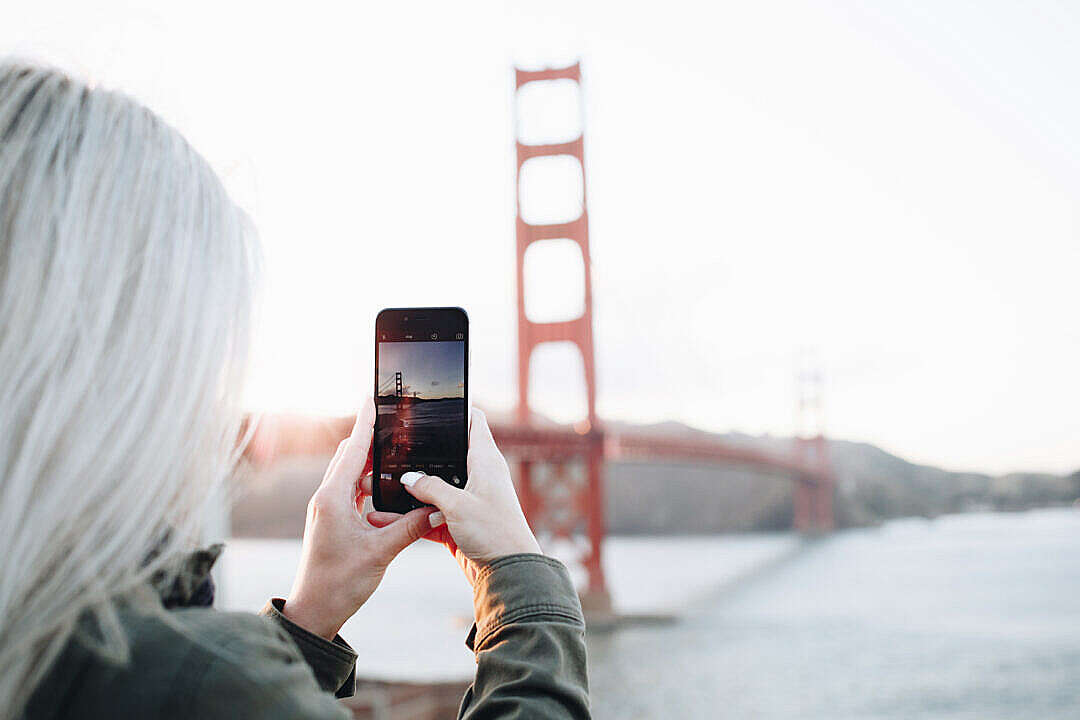 Download Woman Taking a Photo of The Golden Gate Bridge FREE Stock Photo