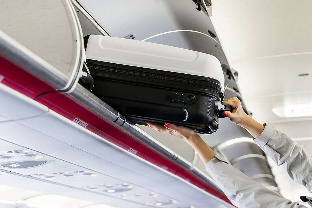 Download Woman Taking Her Hand Luggage in Airplane FREE Stock Photo