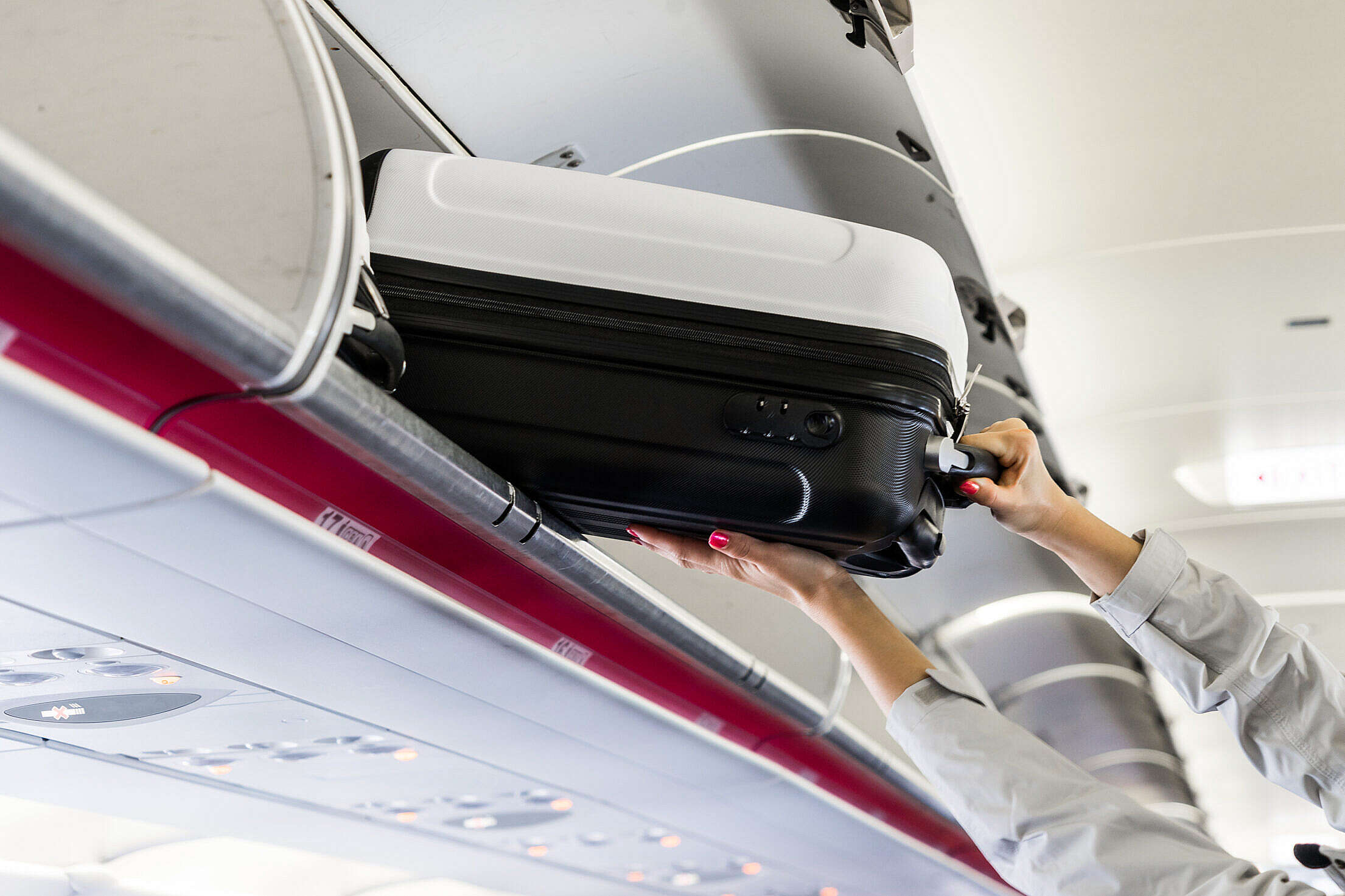 Woman Taking Her Hand Luggage in Airplane Free Stock Photo