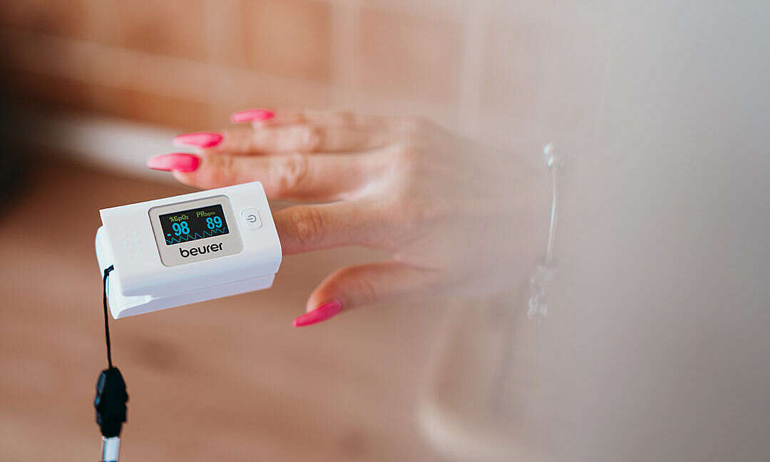 Download Woman Using a Pulse Oximeter to Check Her Oxygen Saturation FREE Stock Photo