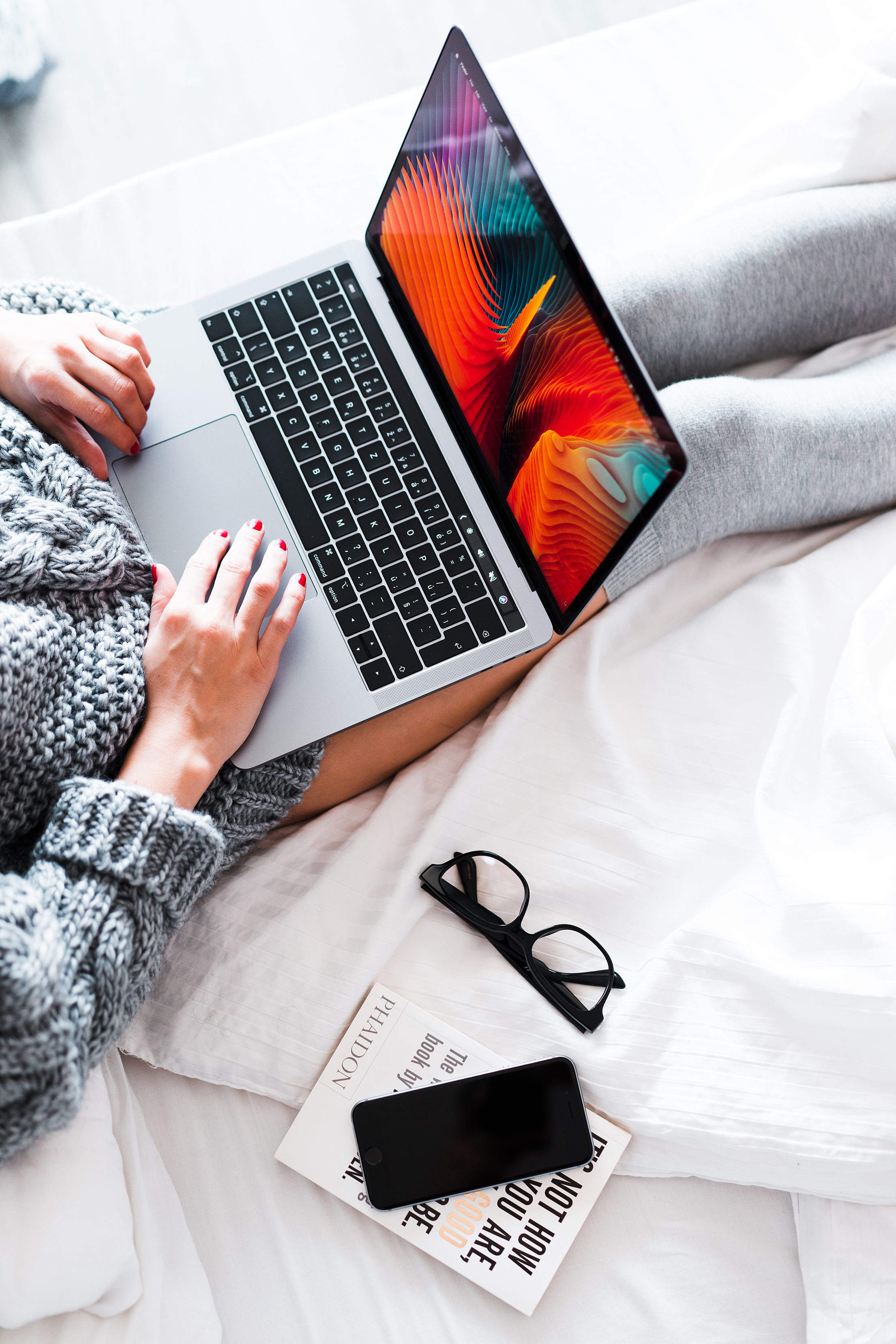 Download Woman Using Her New MacBook in Bed Free Stock Photo