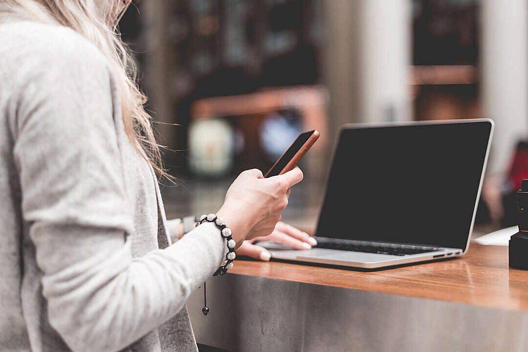 Download Woman Using Her Smartphone While Working Remotely on Laptop FREE Stock Photo