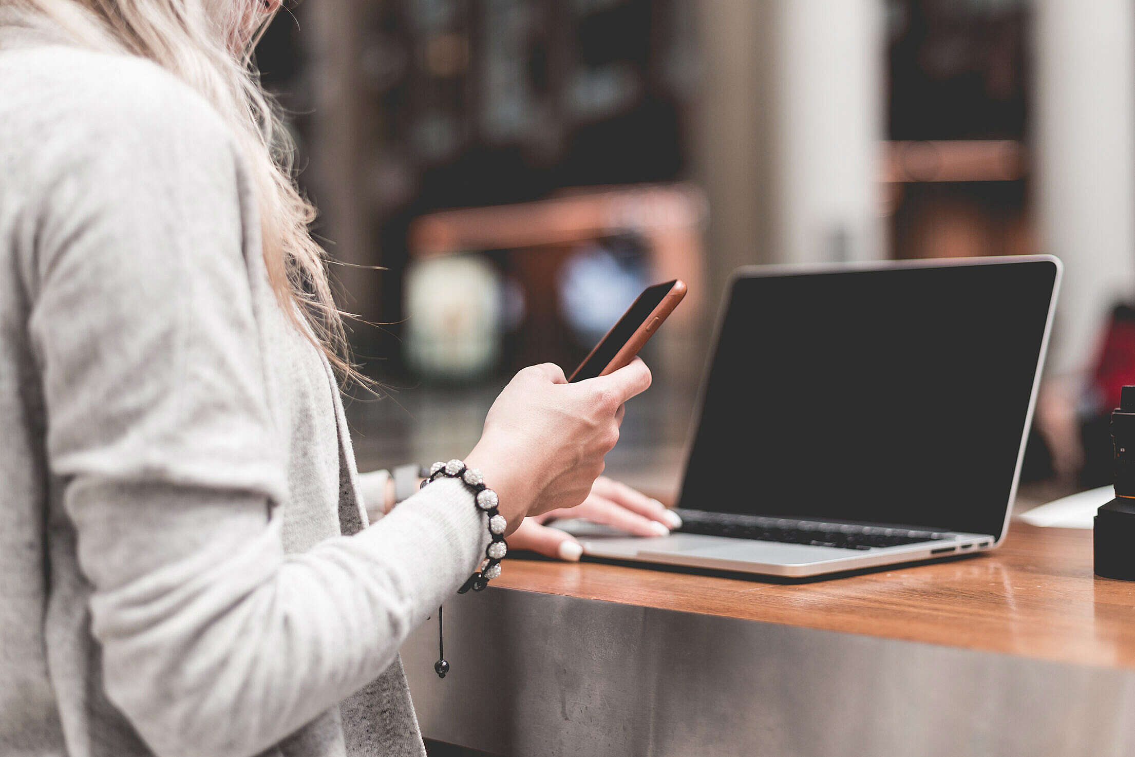 Woman Using Her Smartphone While Working Remotely on Laptop Free Stock Photo