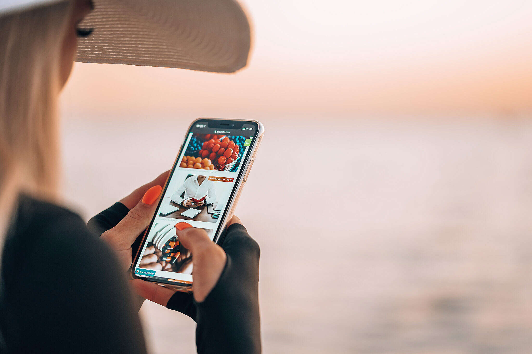 Woman Using Smartphone During Golden Hour by the Sea Free Stock Photo