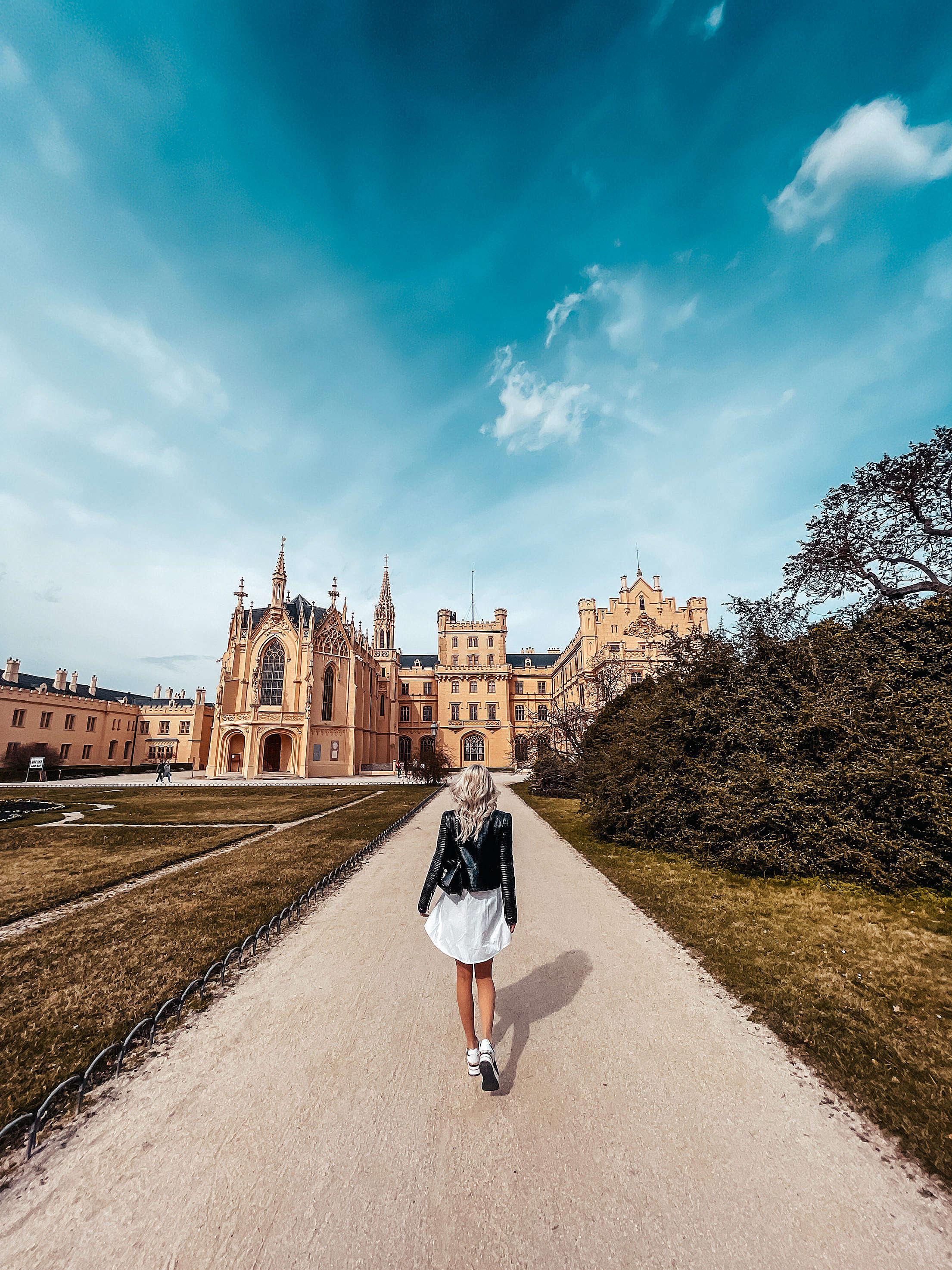 Woman Walking in Lednice Park to Visit Lednice Castle, Czechia Free Stock Photo