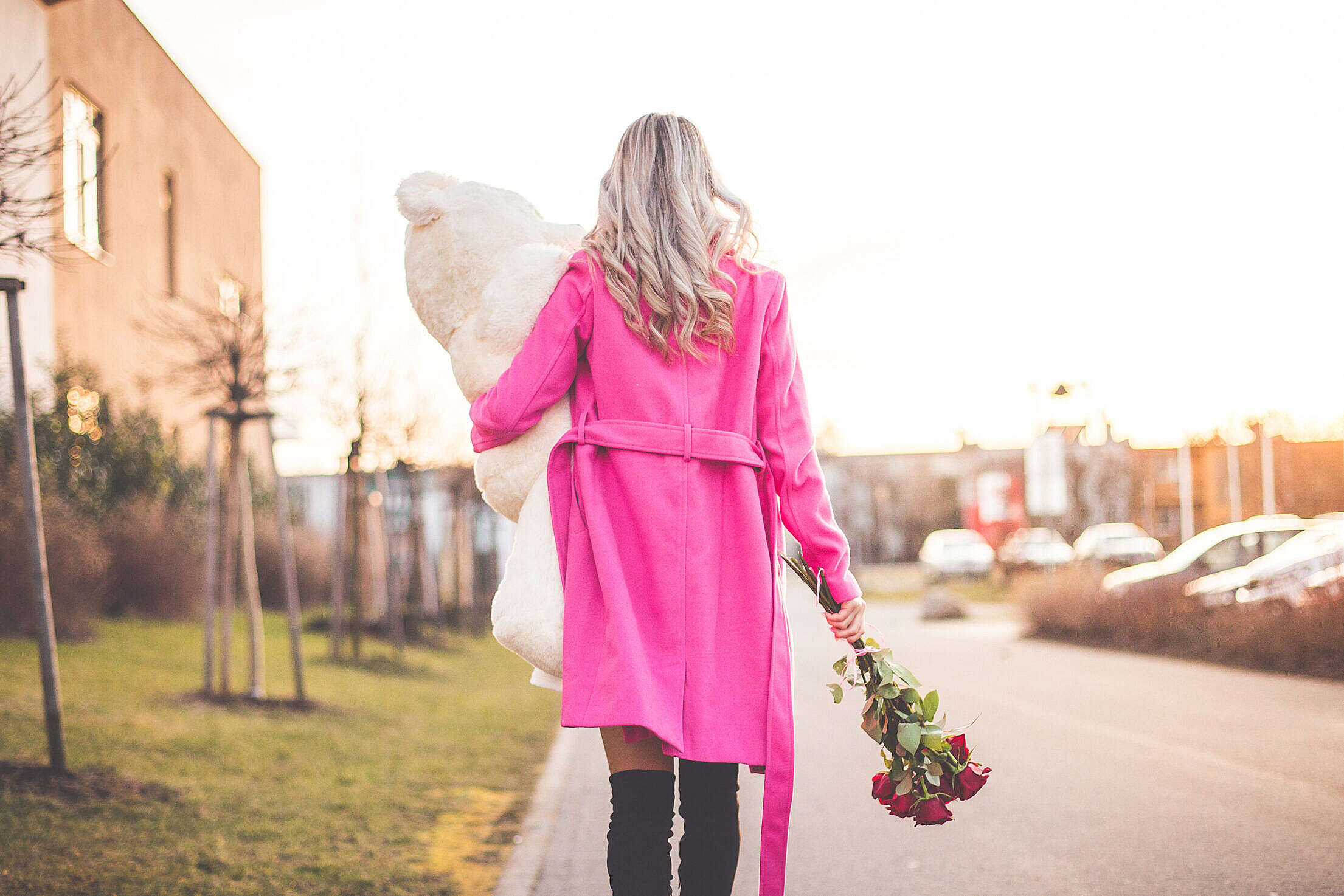 Woman with Big Teddy and Roses Walking on the Street Free Stock Photo
