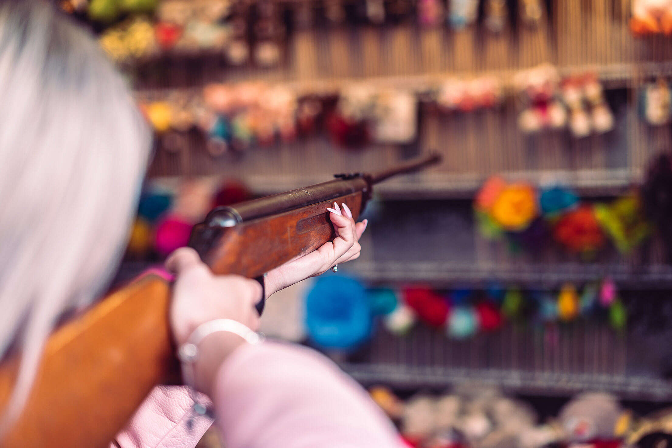 Woman with Rifle at Fun Fair Shooting Range Free Stock Photo