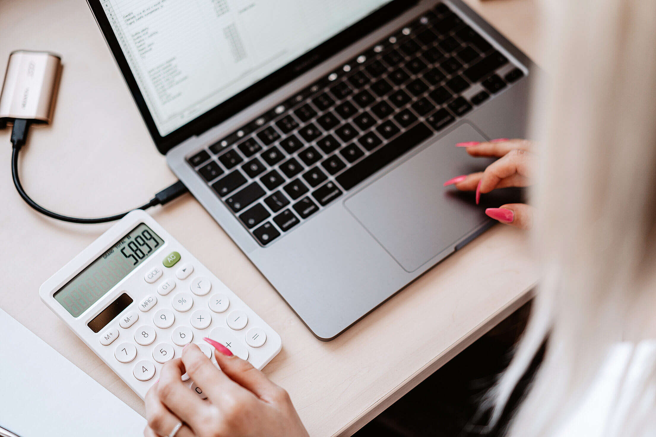 Woman Working on a Laptop and Calculator Free Stock Photo