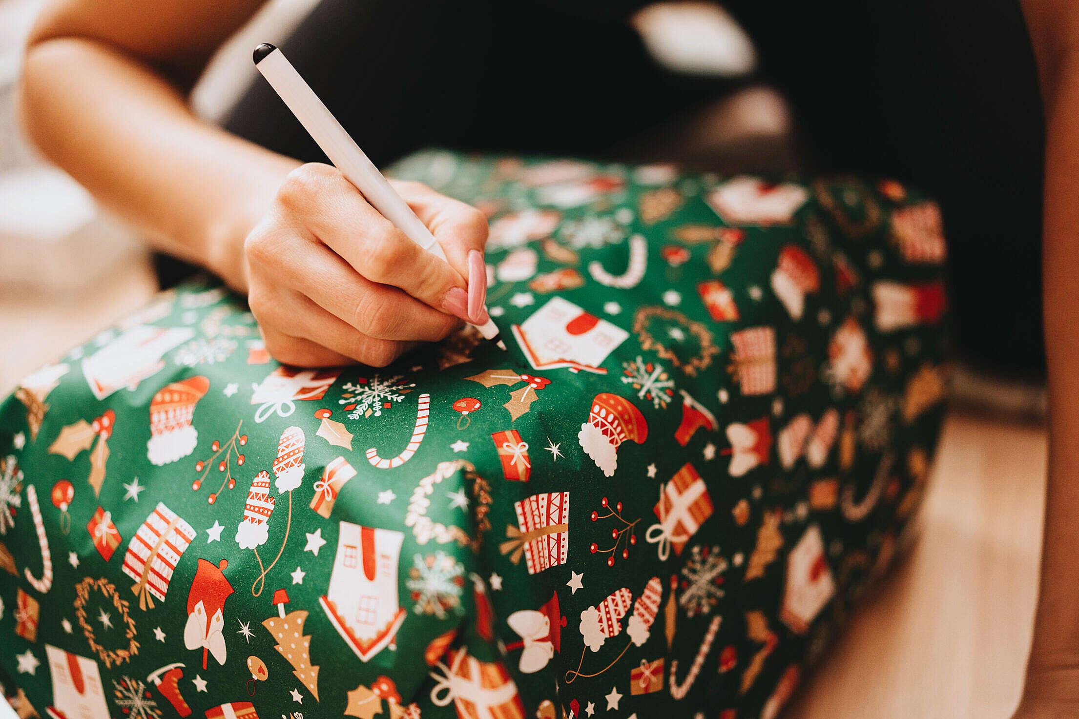 Woman Writing a Name on a Christmas Present Free Stock Photo