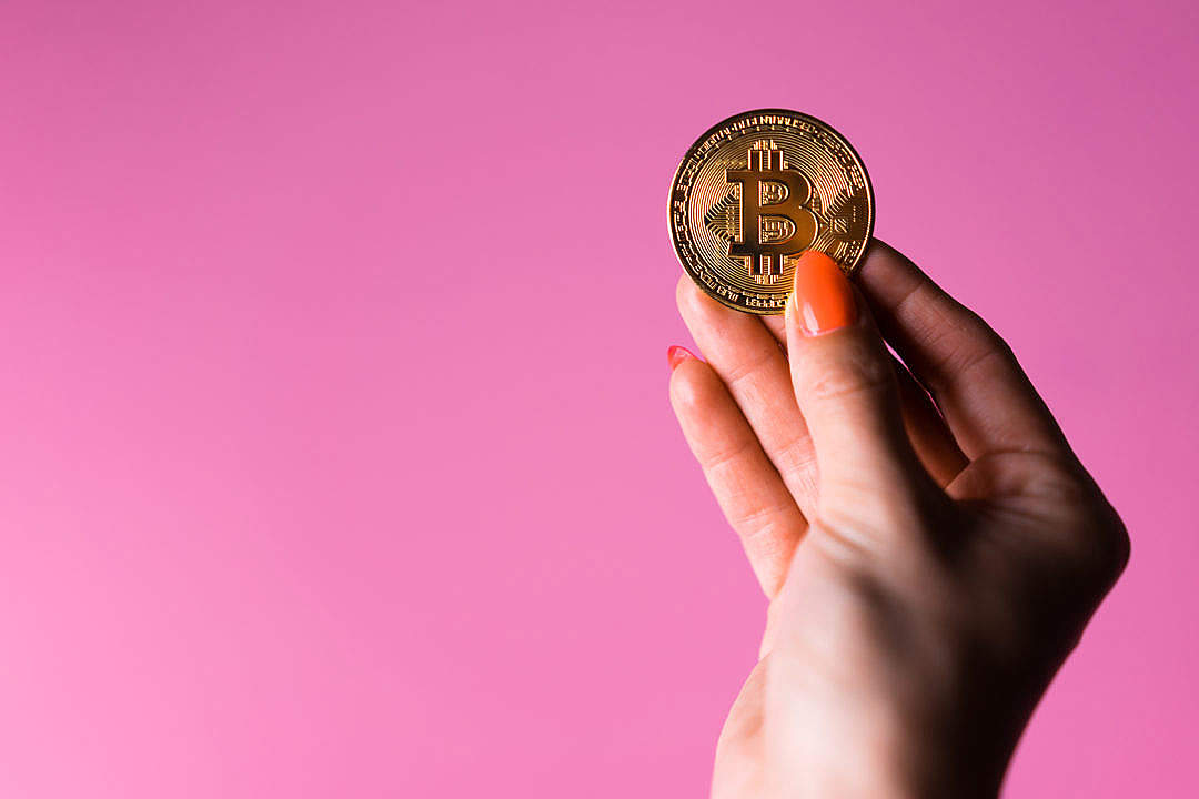 Download Woman's Hand with a Glowing Gold Bitcoin on a Pink Background FREE Stock Photo