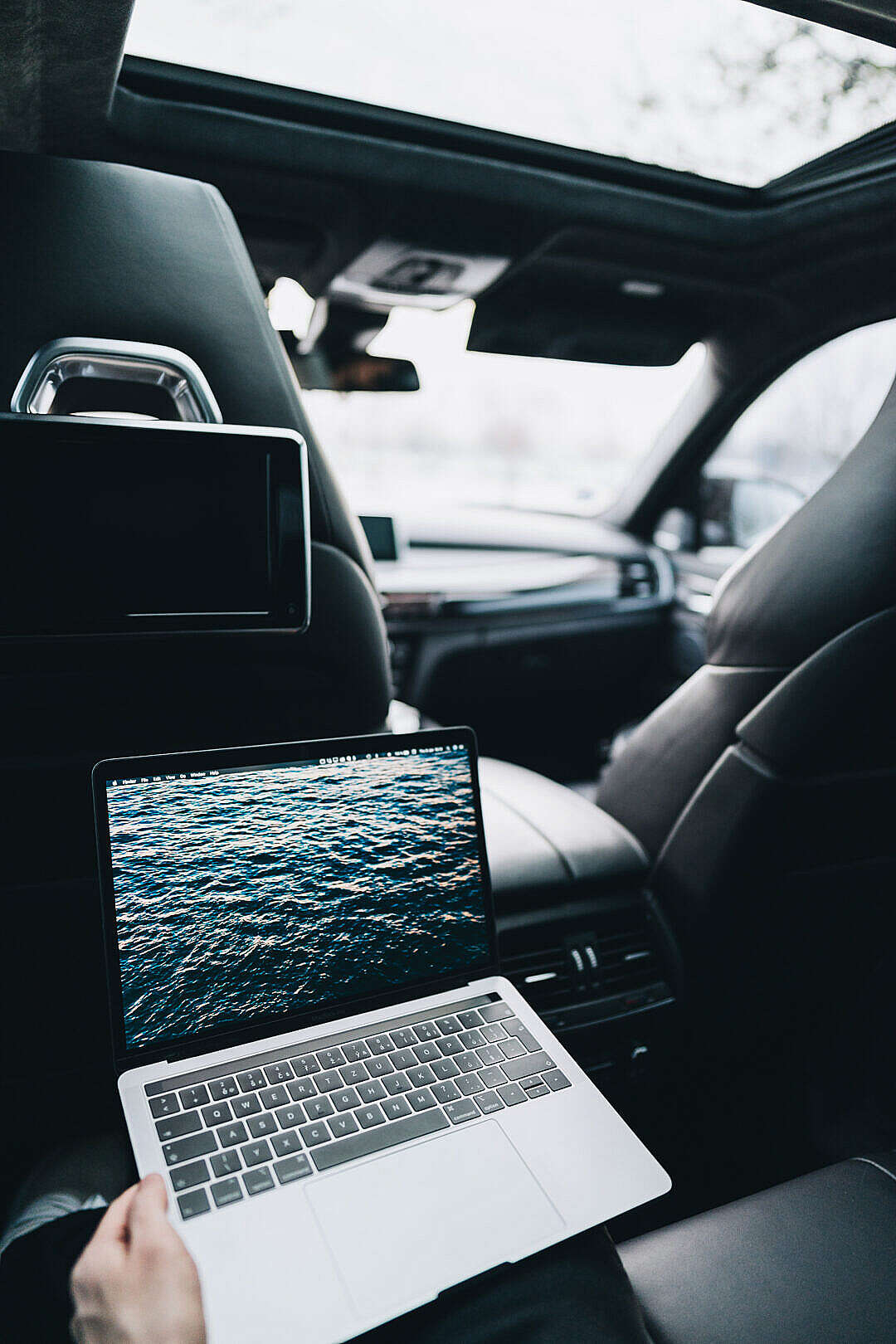 Download Working on a MacBook on Rear Seats in a Car FREE Stock Photo