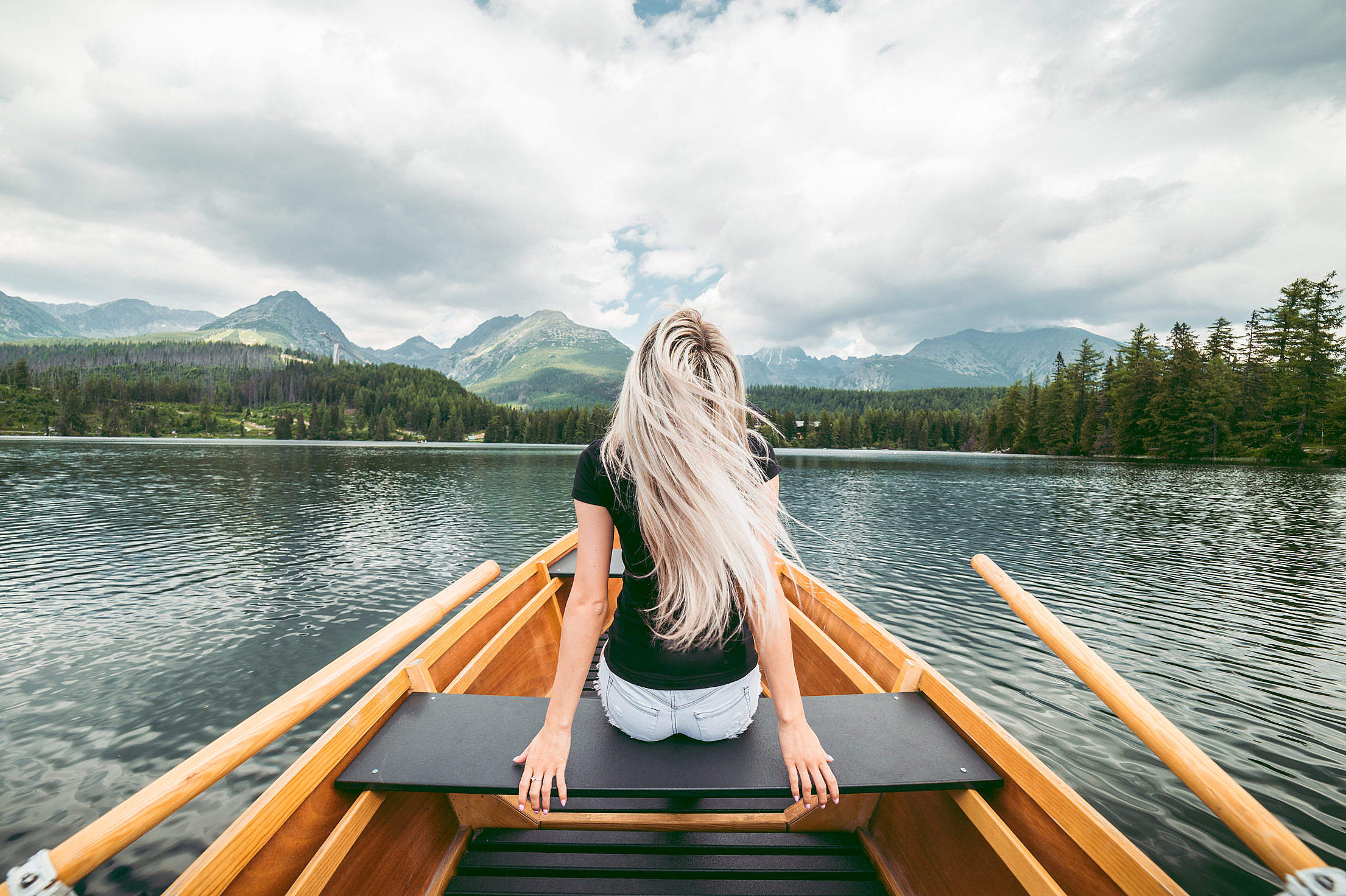 Young Blonde Woman Enjoying a Rowing Boat Free Stock Photo